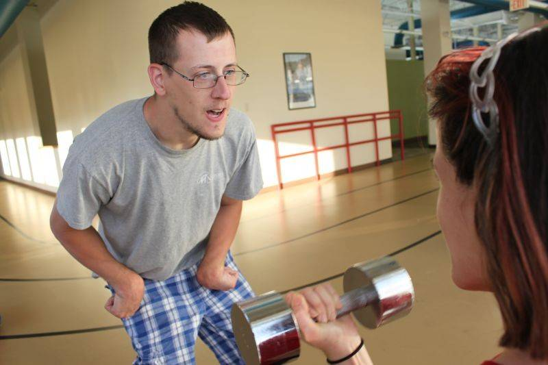 Michael Crawford coaches a participant in NEDSRA's Adaptive Power Lifting program.