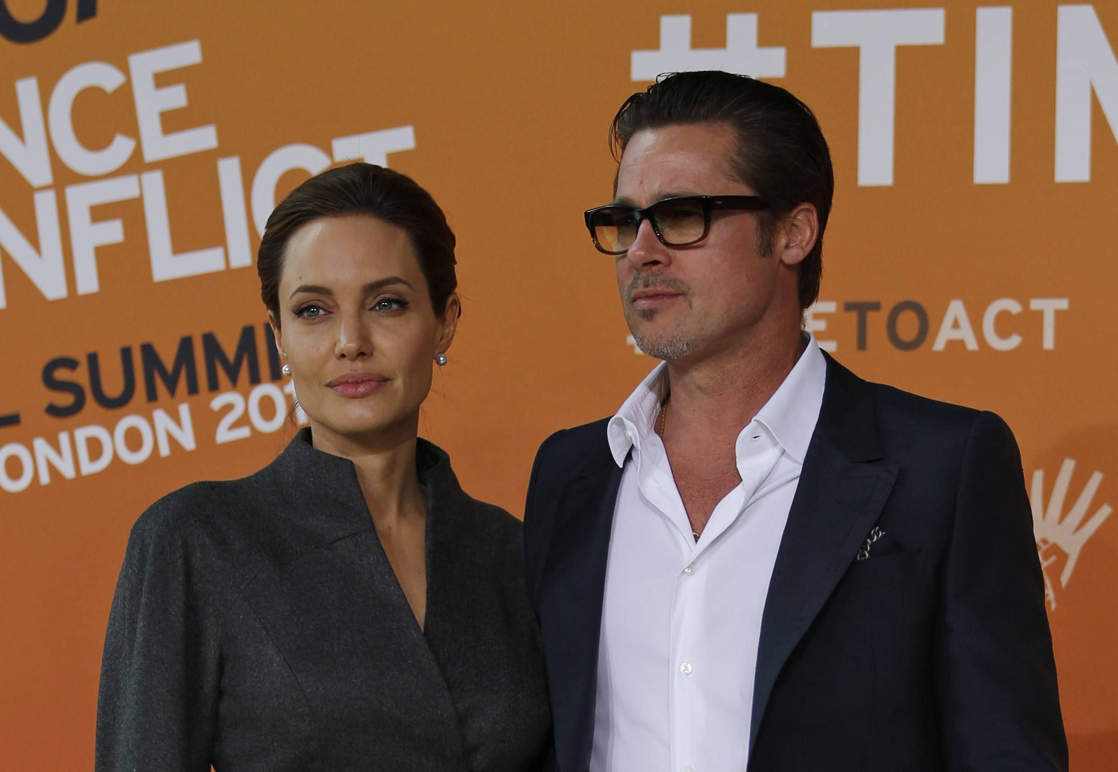 Angelina Jolie, left, special Envoy of the United Nations high commissioner for refugees, accompanied by her partner, actor Brad Pitt, pose for the photographers as they arrive at the End Sexual Violence in Conflict summit Friday in London. Jolie was named an honorary dame by Queen Elizabeth II for her work combating sexual violence in war zones.