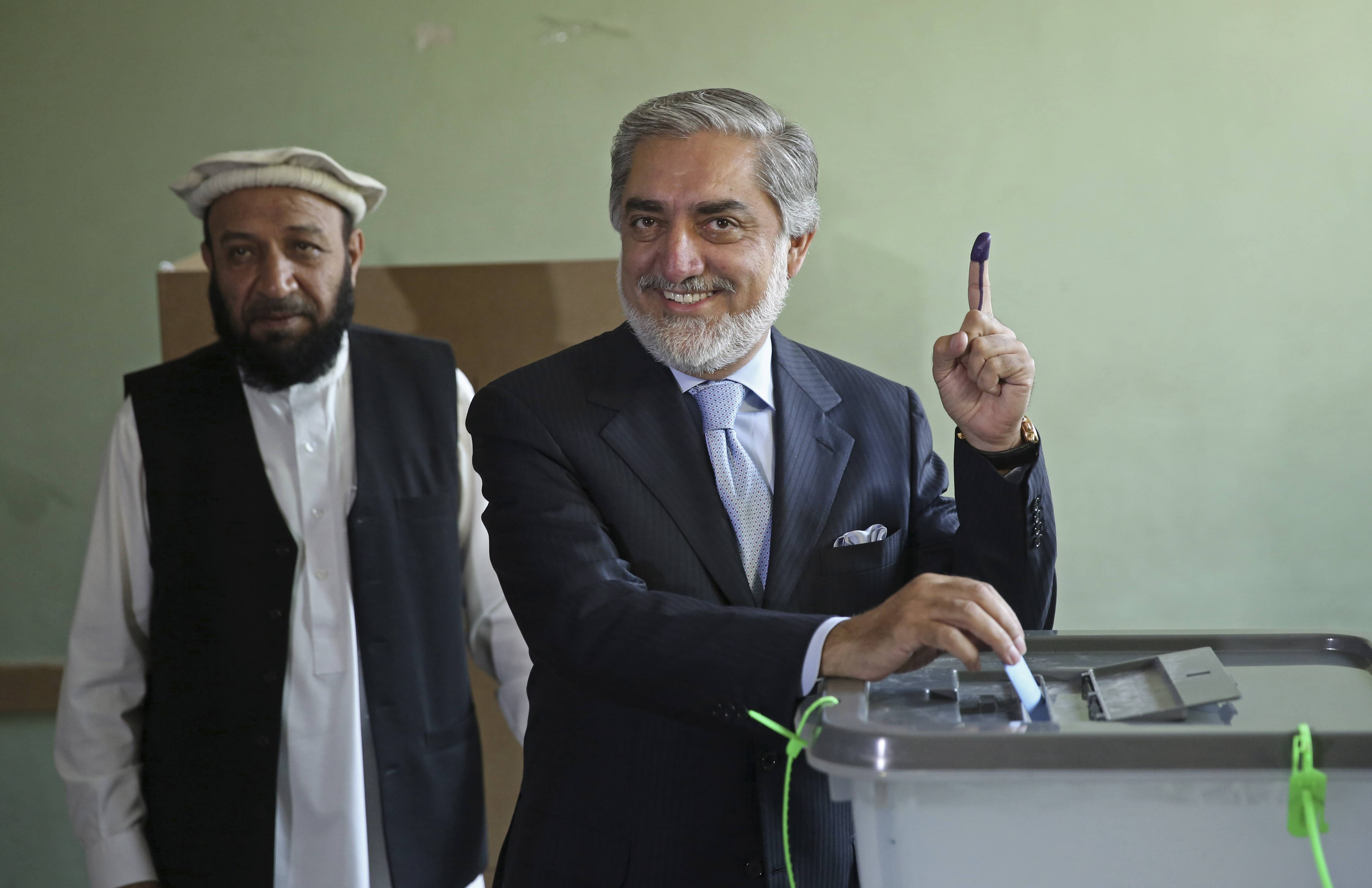 Afghanistan's presidential candidate Abdullah Abdullah, right, poses for photos Saturday before he casts his vote as his vice president candidate, Mahoammad Khan, left, waits at a pooling station in Kabul, Afghanistan.