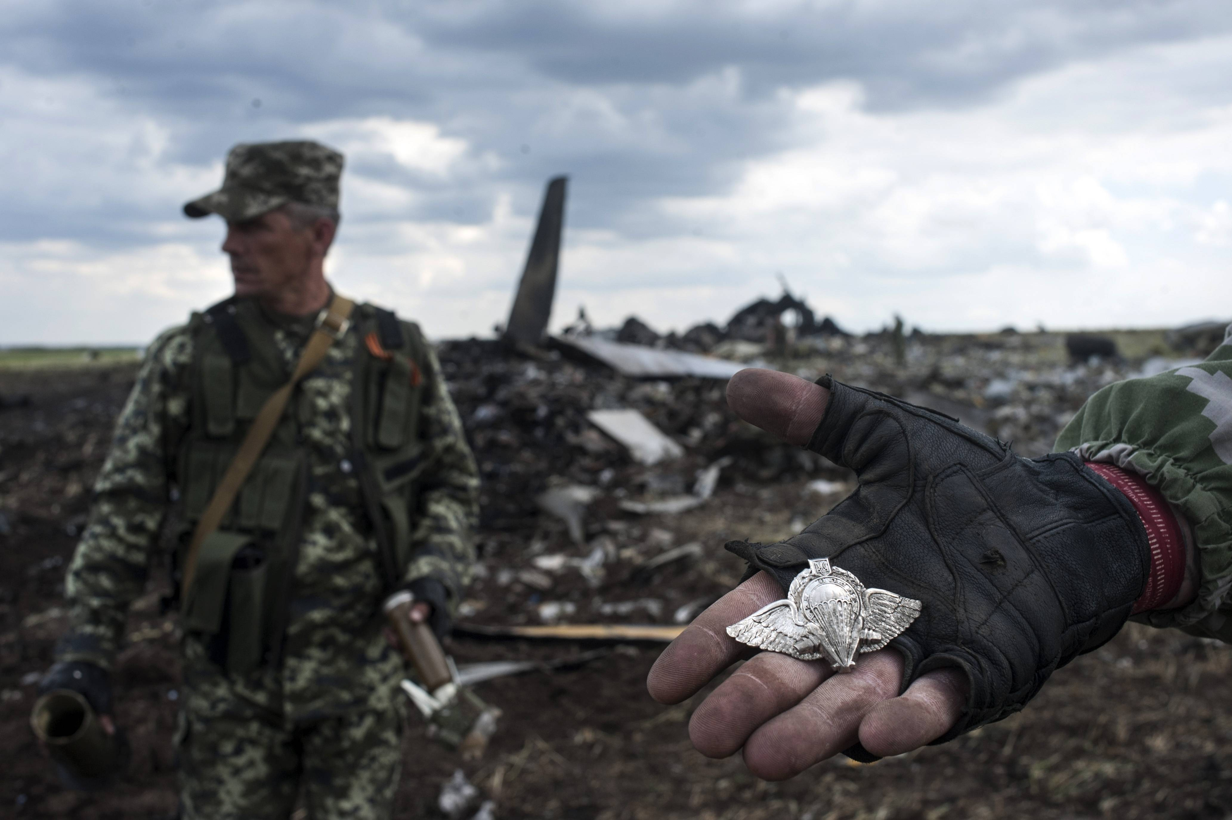 A pro-Russian fighter shows a Ukrainian paratroopers emblem as the other one carries parts of weapons form the site of remnants of a downed Ukrainian army aircraft Il-76 at the airport near Luhansk, Ukraine, Saturday, June 14. Pro-Russian separatists shot down the military transport plane Saturday in the country's restive east, killing all 49 service personnel on board, Ukrainian officials said.