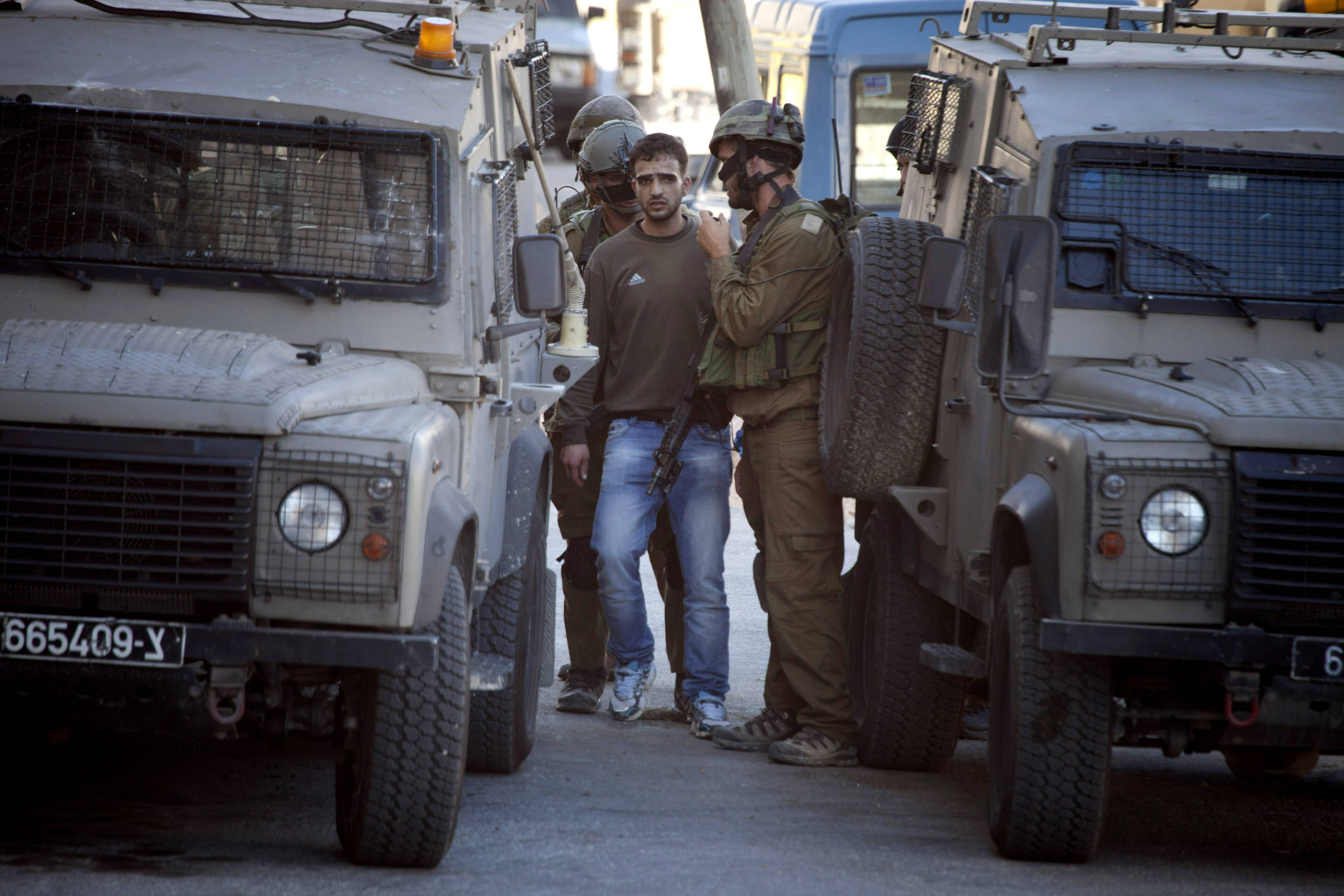 Israeli soldiers arrest a Palestinian man in the West Bank City of Hebron, Saturday, June 14. Israeli security forces searched the West Bank for a second day Saturday, looking for three missing teenagers, including a U.S. citizen, who they fear have been abducted by Palestinian militants.