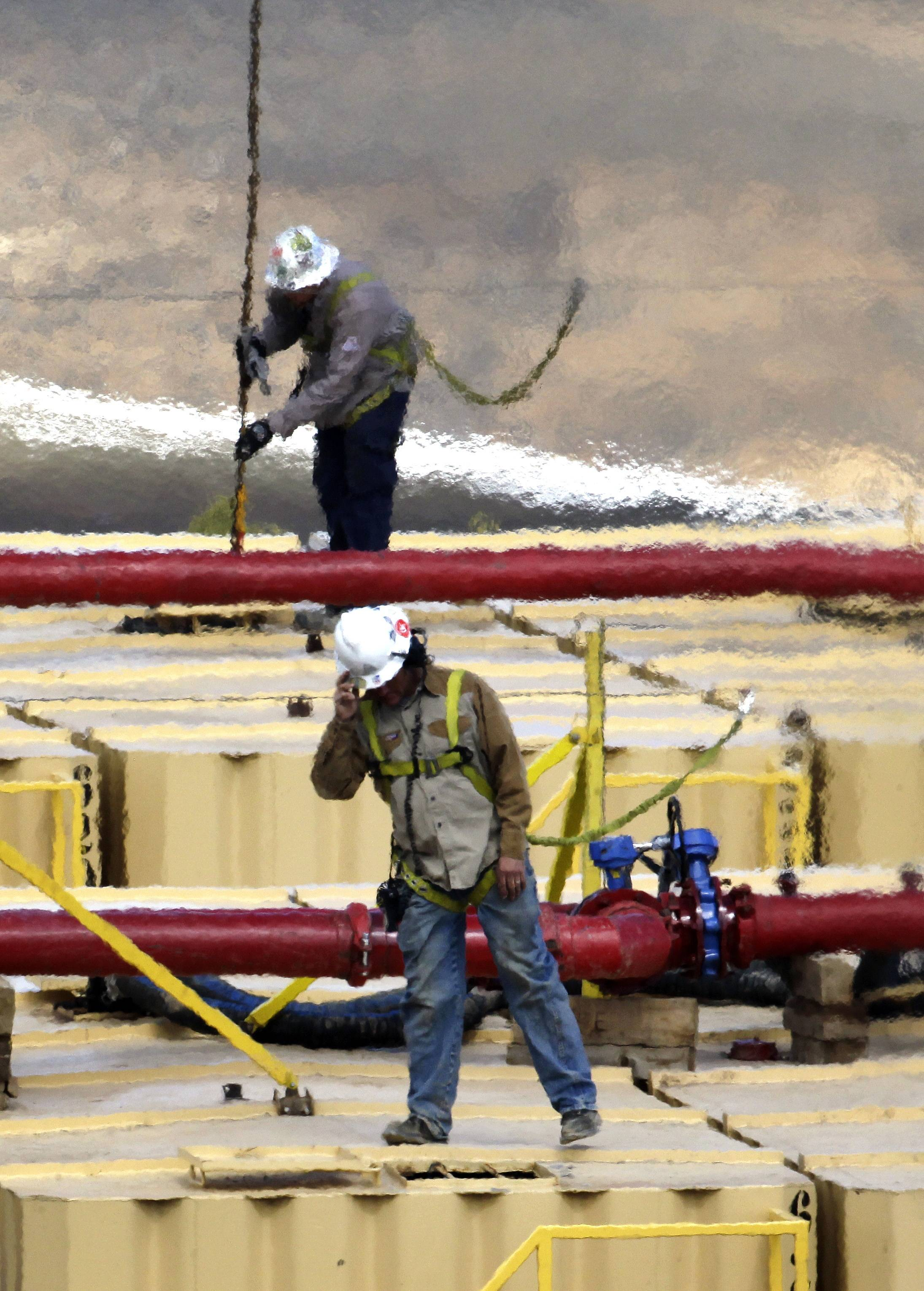 Workers standing atop water tanks while they help keep an eye on water pressure and temperature at an oil and gas hydraulic fracturing site outside Rifle, Colo.