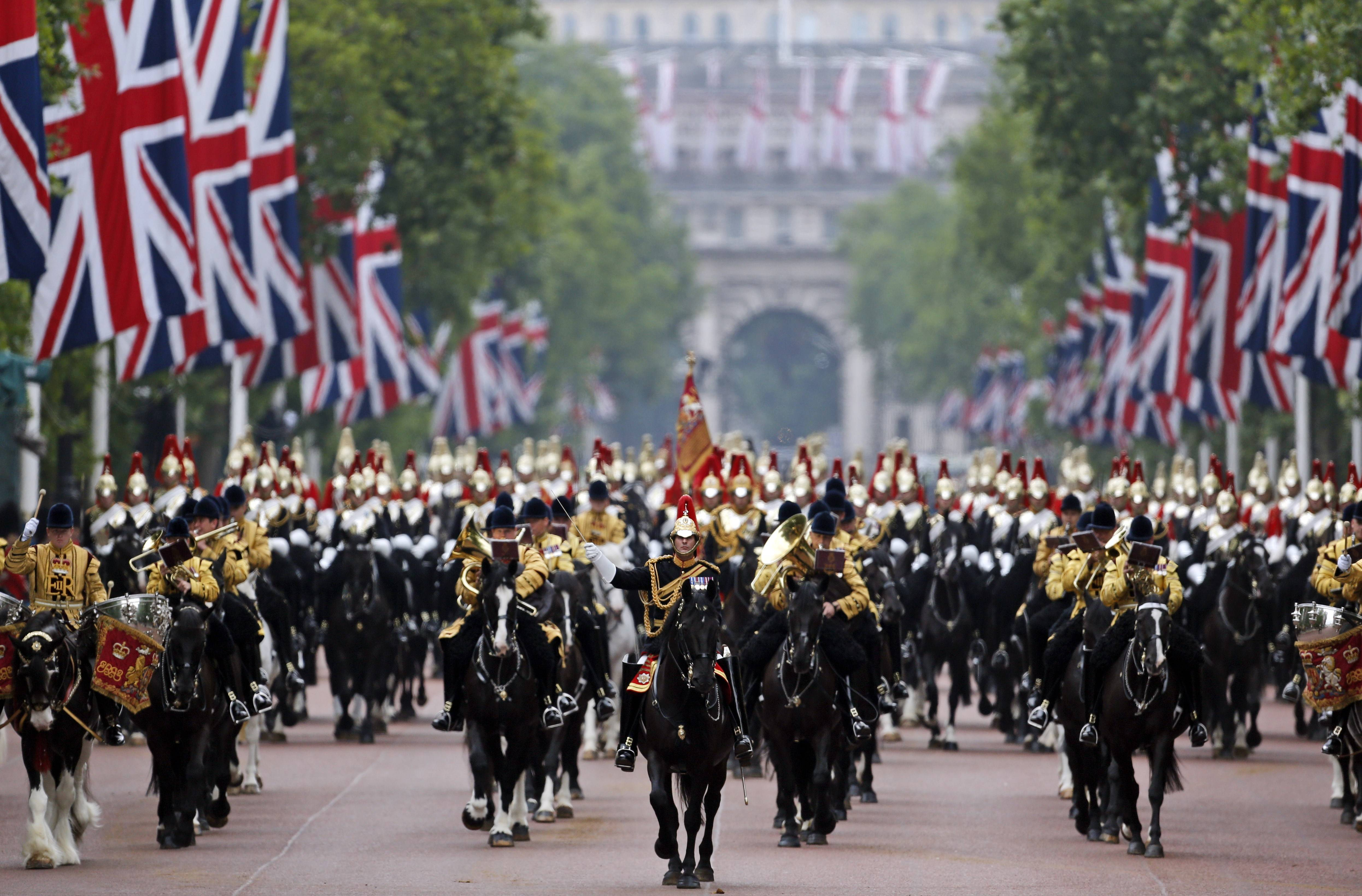 "British soldiers ride their horses as the escort Queen Elizabeth II in a horse drawn carriage as she returns to Buckingham Palace, during the Trooping The Colour parade, in central London, Saturday, June 14. Hundreds of soldiers in ceremonial dress have marched in London in the annual ""Trooping the Color"" parade to mark the official birthday of Queen Elizabeth II. ""Trooping the Colour"" originated from traditional preparations for battle, when flags were carried or ""trooped"" down the rank for soldiers to see."