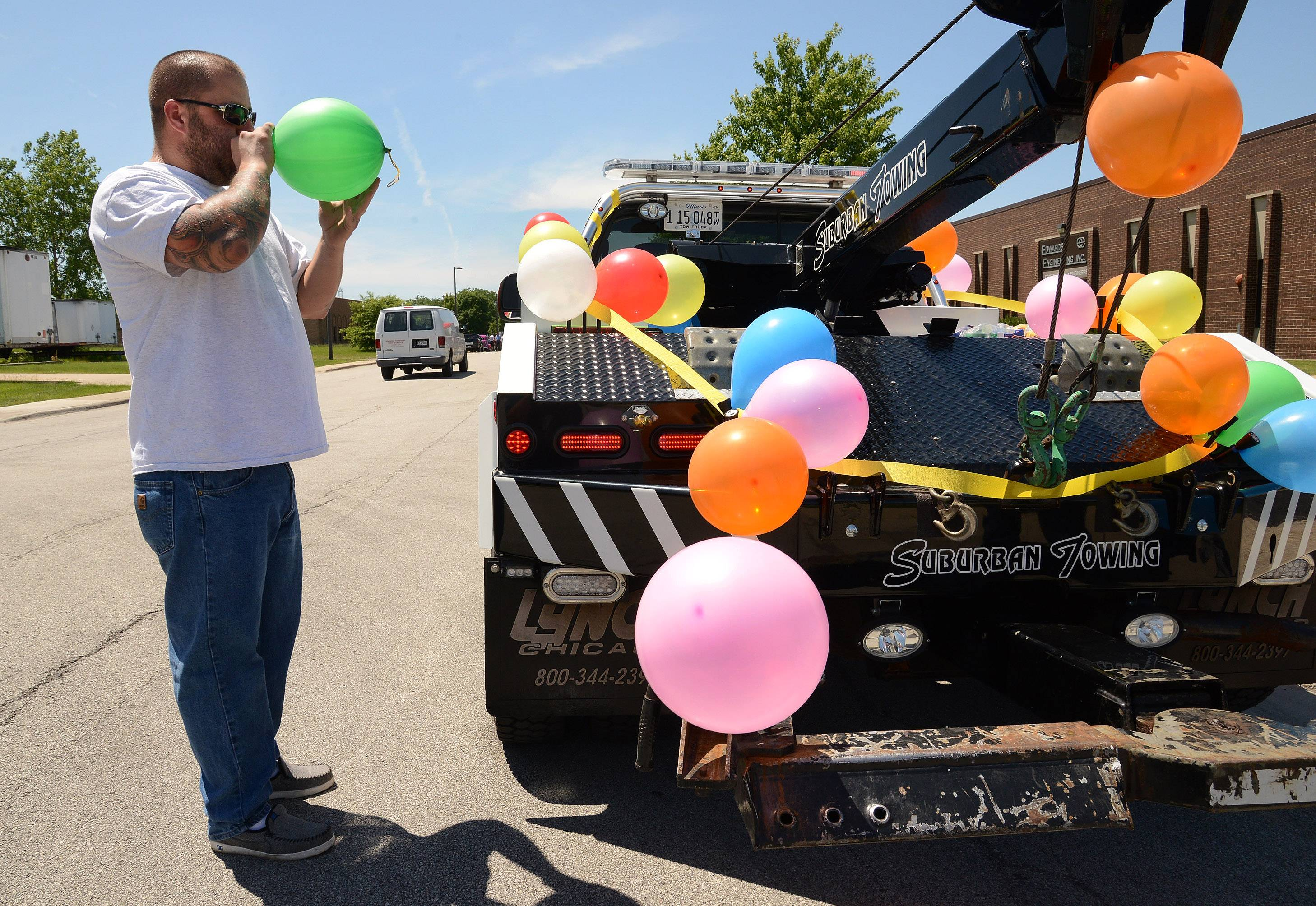 Chris Little of Suburban Towing and Recovery was blowing up balloons to decorate his truck Saturday afternoon for the parade in Elk Grove Village.