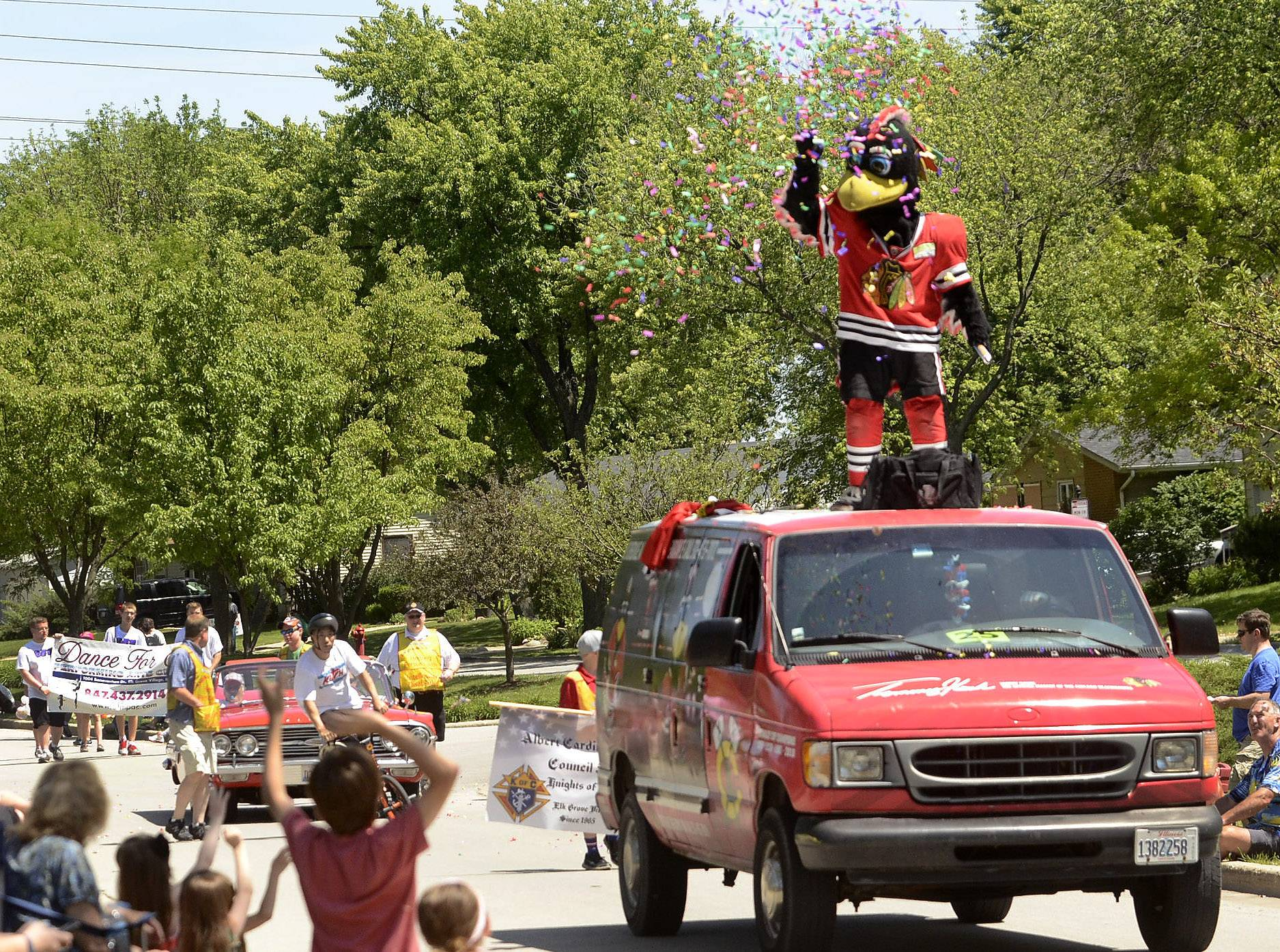 Chicago Blackhawks mascot Tommy Hawk blows off confetti Saturday afternoon along the route during the 2014 Elk Grove Hometown Parade, which kicked off at Tonne Road and Elk Grove Boulevard.