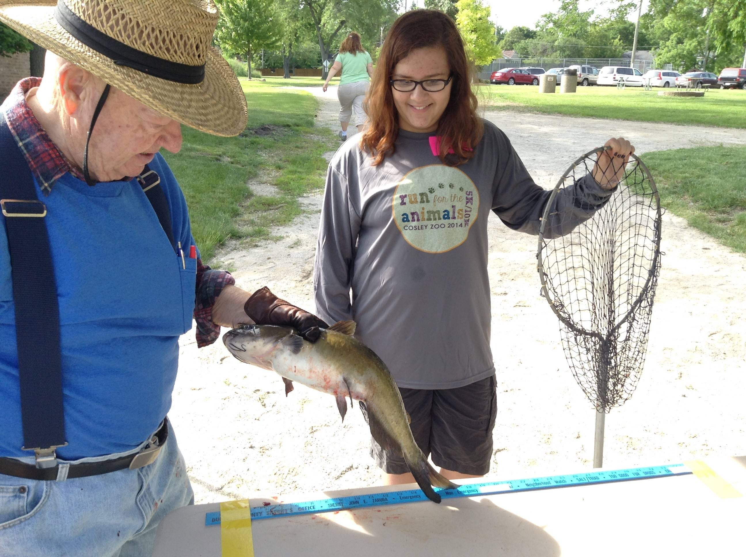 Jim Smith of the Kiwanis Club of Wheaton receives a 24¼-inch catfish from Meghan Aragon of Wheaton to measure and enter into the Wheaton Park District's Fish-O-Rama fishing competition at Northside Park Saturday. Aragon's catfish came in second place in the day's biggest fish category.