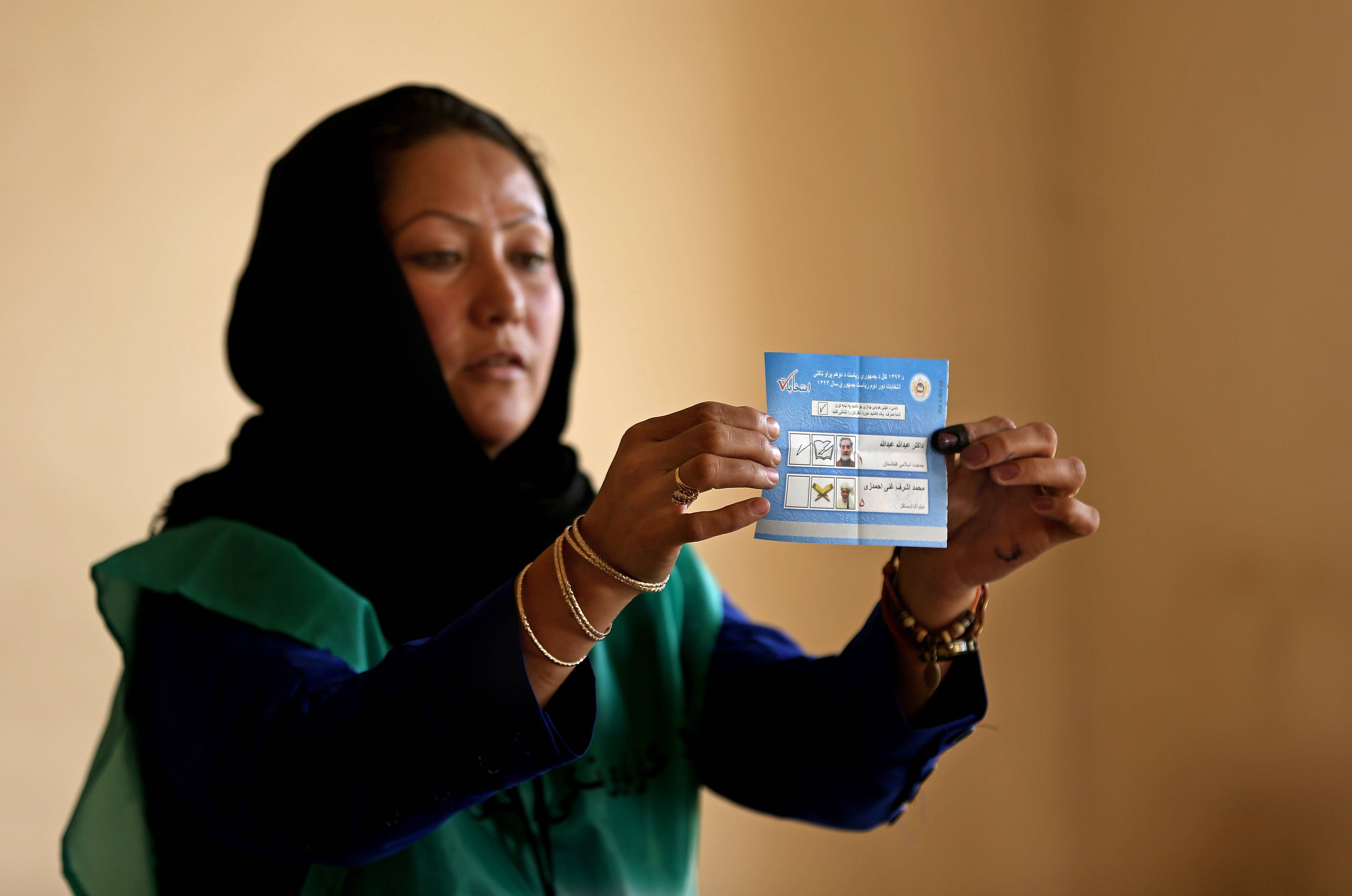 An Independent Election Commission (IEC) employee shows a ballot to observers Saturday at a polling station in Kabul, Afghanistan.
