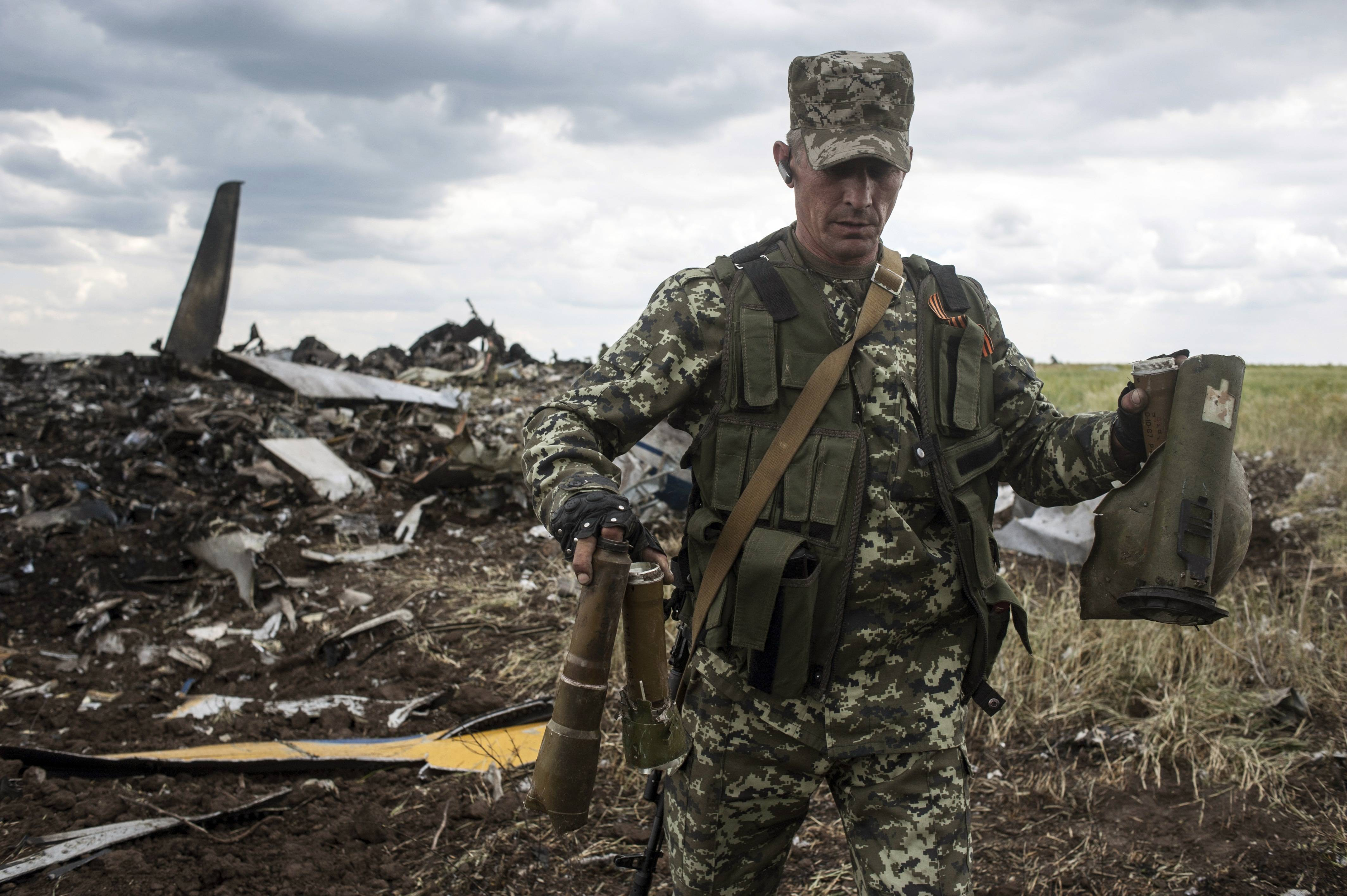 A pro-Russian fighter carries parts of weapons Saturday from the site of remnants of a downed Ukrainian army aircraft Il-76 at the airport near Luhansk, Ukraine.