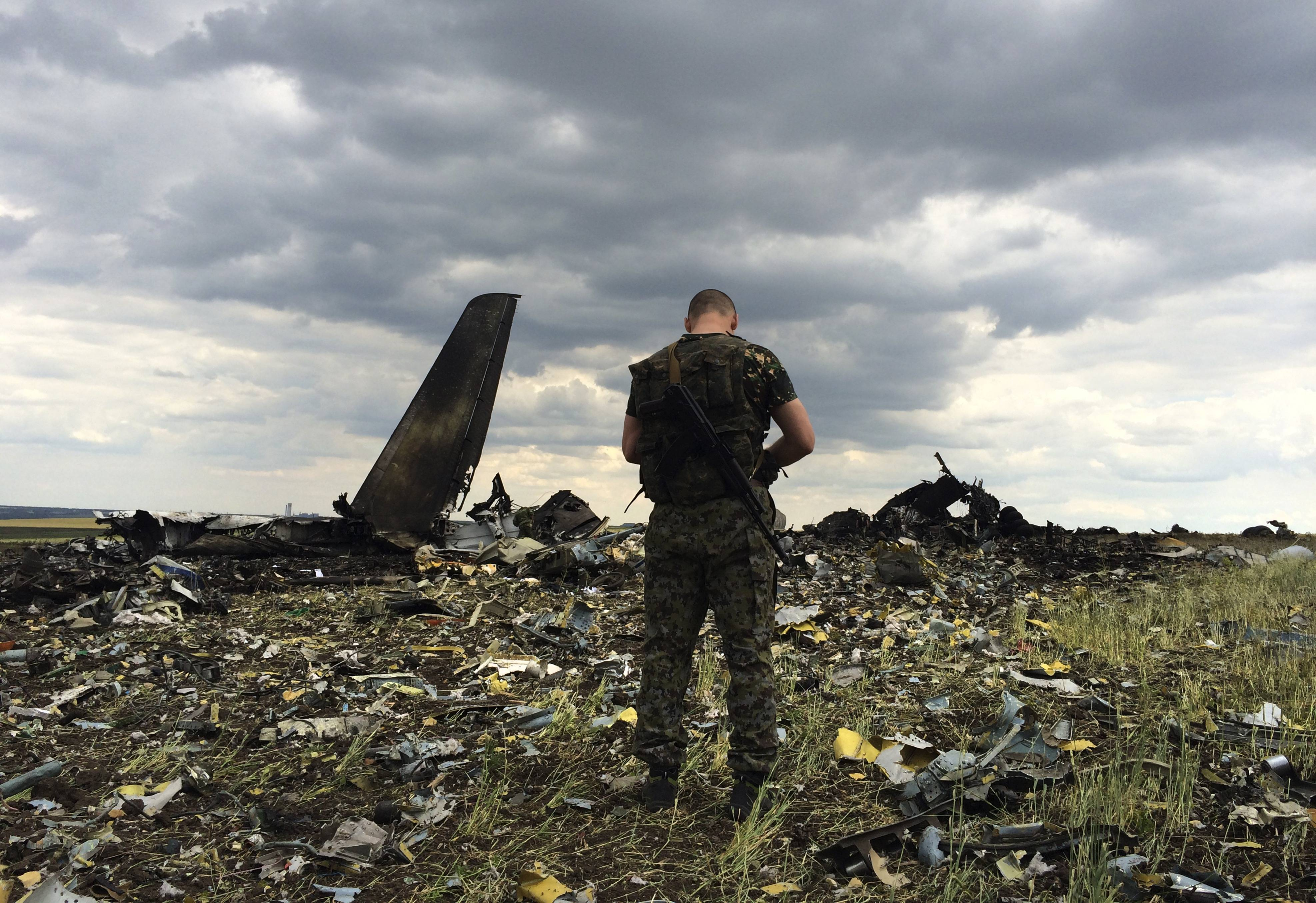 A pro-Russian fighter guards the site Saturday of remnants of a downed Ukrainian army aircraft Il-76 at the airport near Luhansk, Ukraine.