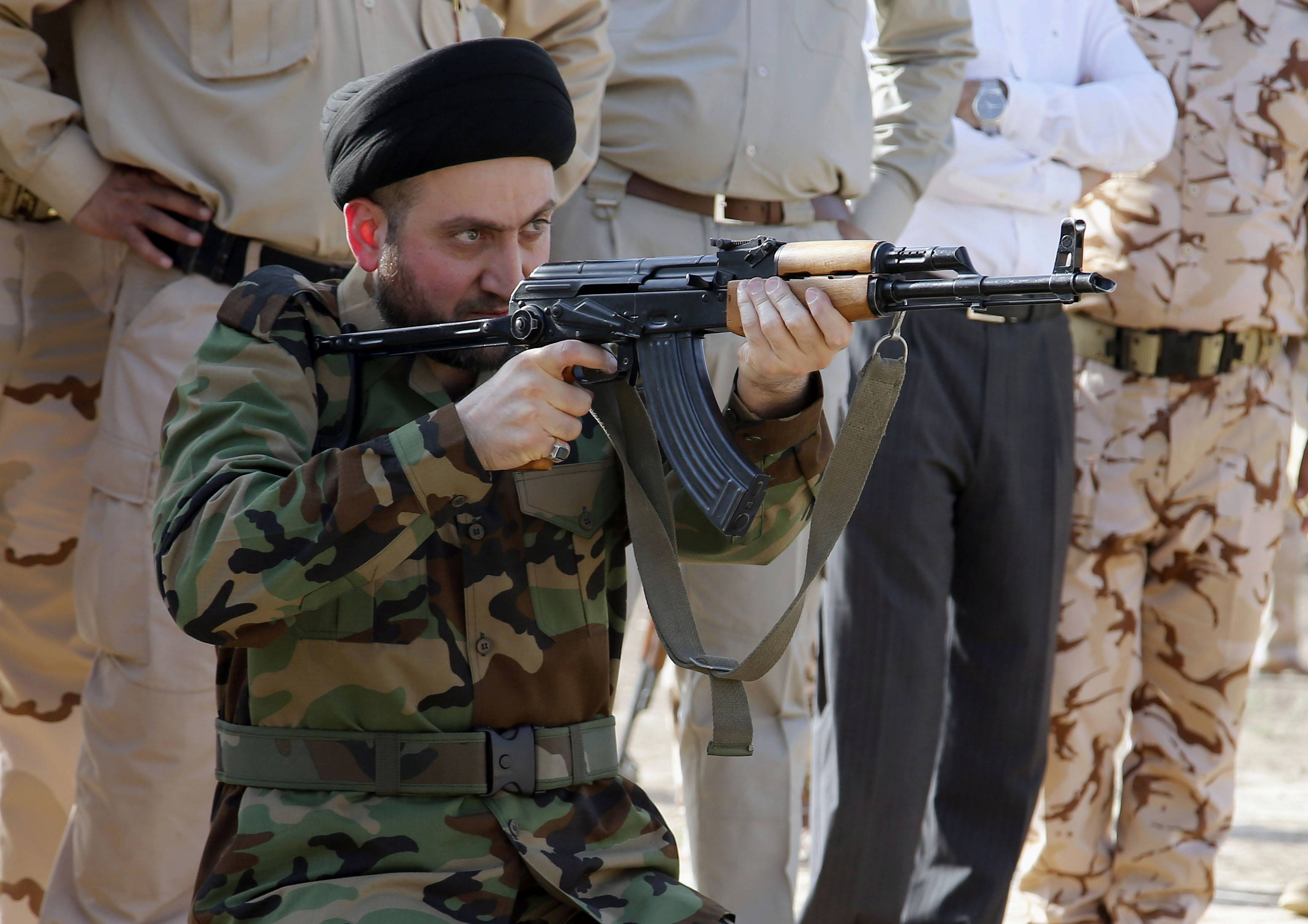 Ammar al-Hakim, leader of Iraq's largest Shiite party, the Supreme Islamic Iraqi Council, exercises a shooting drill in the main army recruiting center in Baghdad, Iraq.