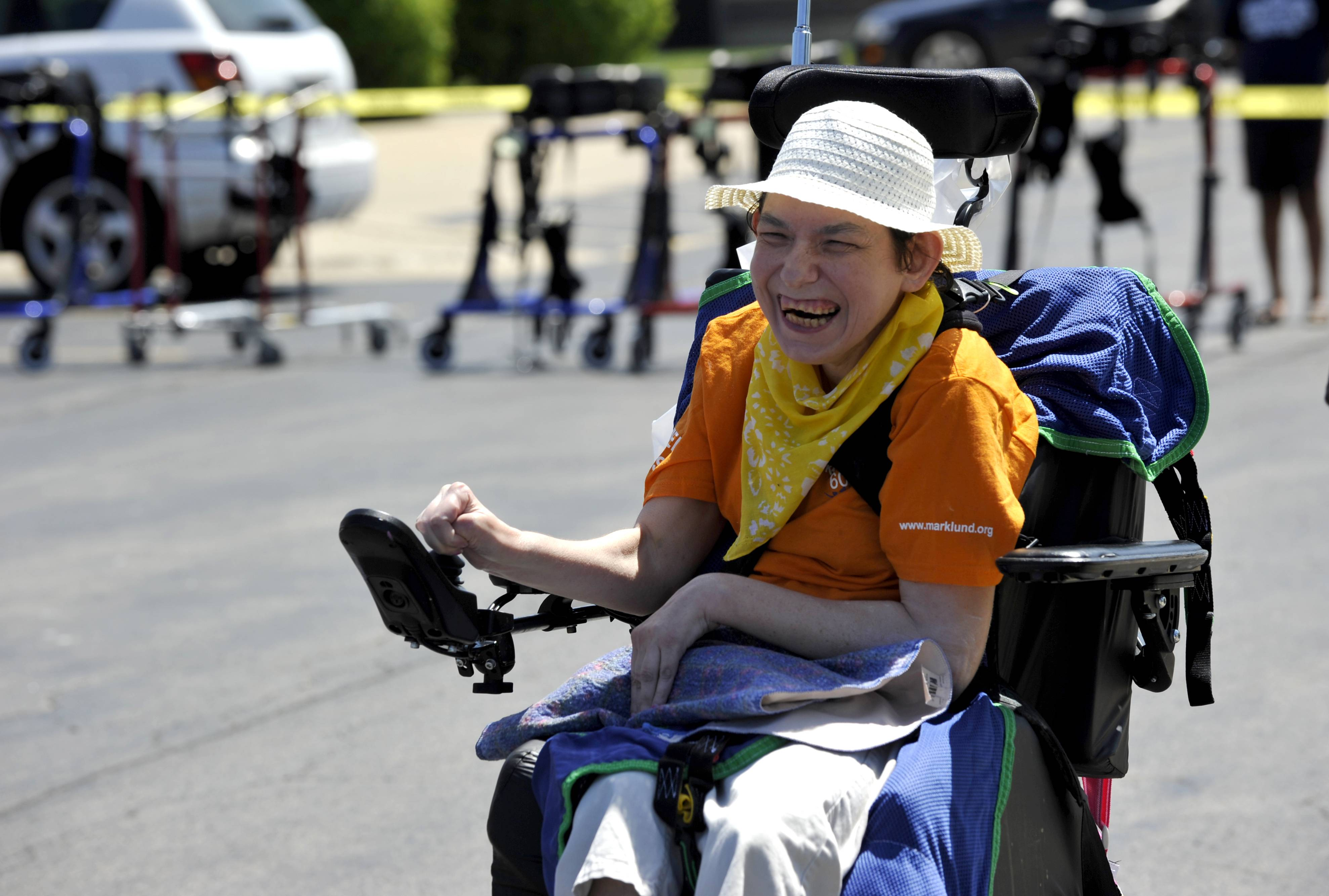 Shelia Sullivan laughs with excitement as she finishes first in the wheelchair race during Marklund's annual Summer Games in Geneva on Saturday.