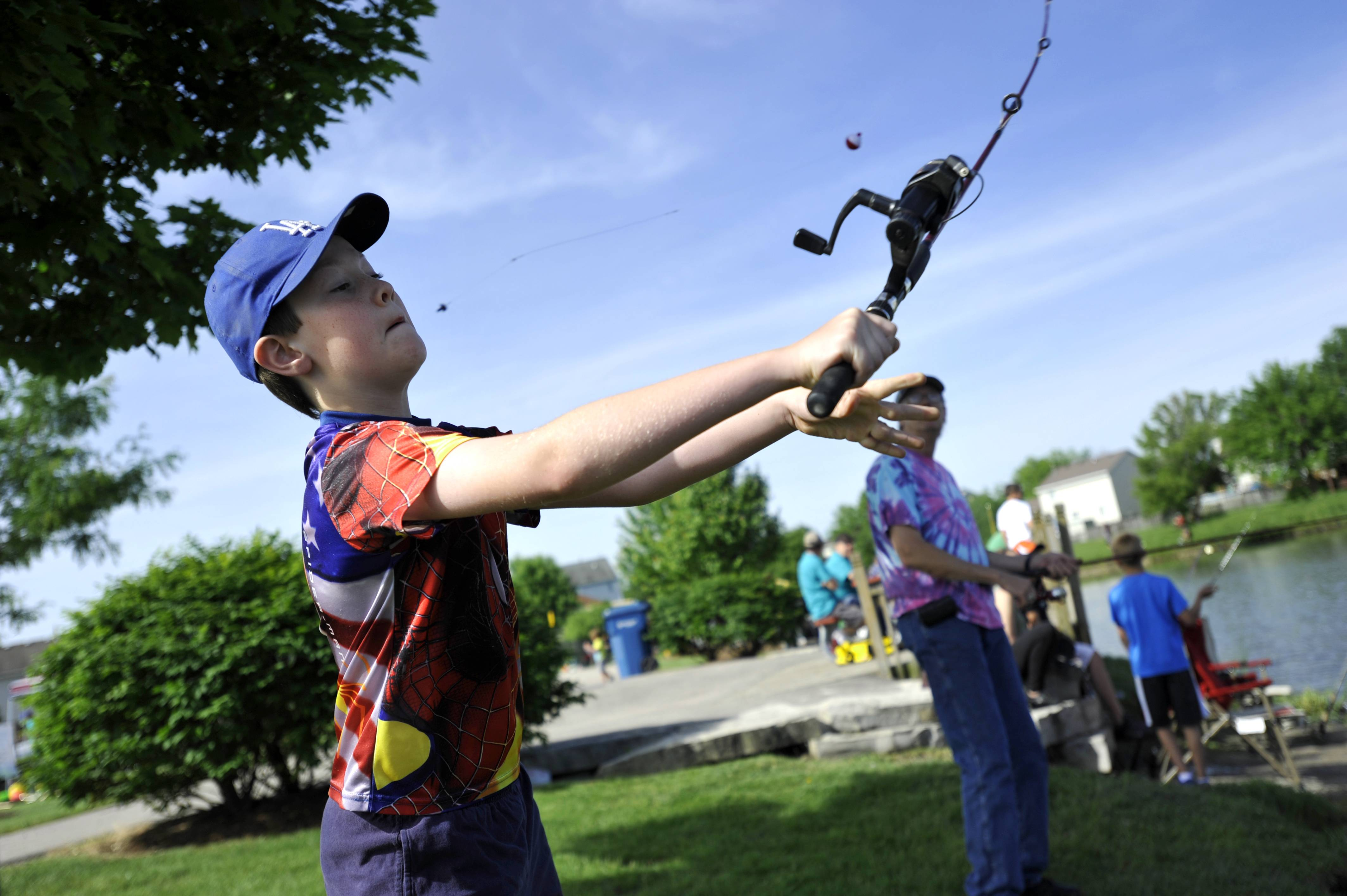 Gavin Johnson, 9, of South Elgin casts his line as his father Scott watches on at the annual Tuna Kahuna Fishing Derby in Blackhawk Park in South Elgin on Saturday. Johnson's grandfathers were both avid fisherman in San Diego and Scott enjoys taking his son fishing on Father's Day weekend.