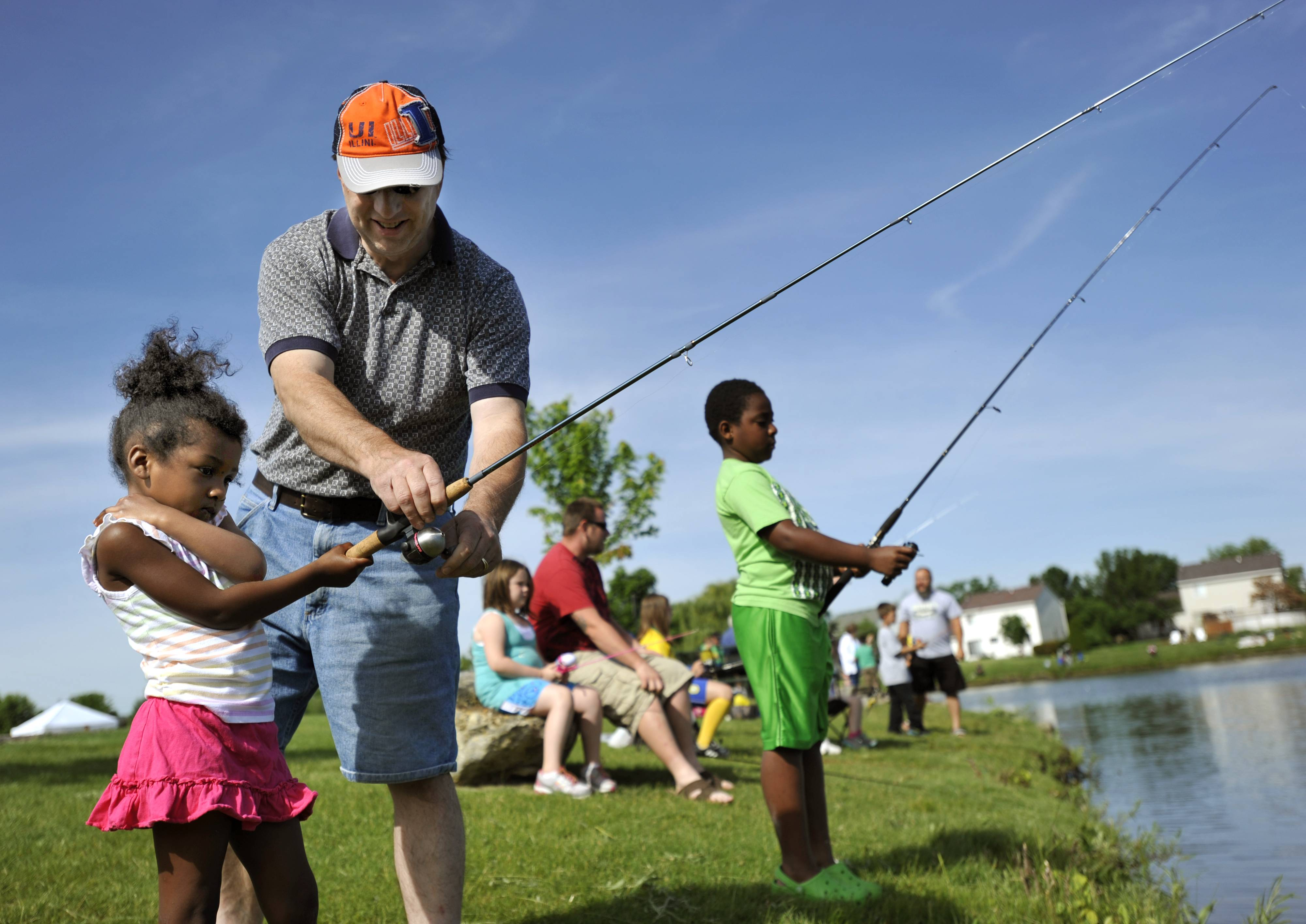 "Mike Hladeck of Elgin helps his daughter Nicole, 4, with her fishing rod while his son Matthew, 8, tries to catch fish at the annual Tuna Kahuna Fishing Derby in Blackhawk Park in South Elgin on Saturday. Hladeck says his wife looks out for the event each year and Nicole says ""I like coming with my dad."""