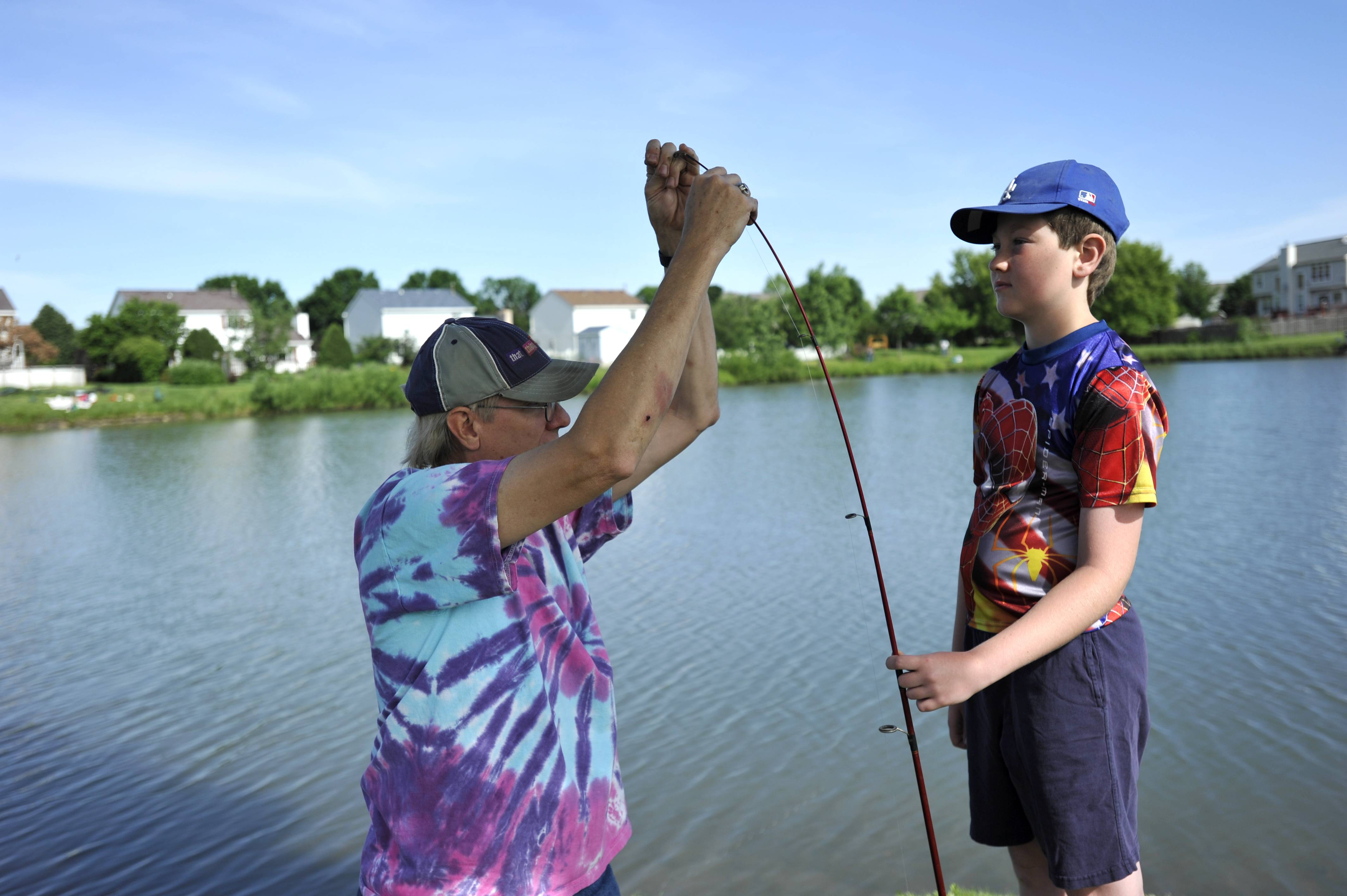 Scott Johnson of South Elgin helps his son Gavin, 9, with his fishing rod at the annual Tuna Kahuna Fishing Derby in Blackhawk Park in South Elgin on Saturday. Johnson's grandfathers were both avid fisherman in San Diego and they enjoy coming to the derby on Father's Day weekend.