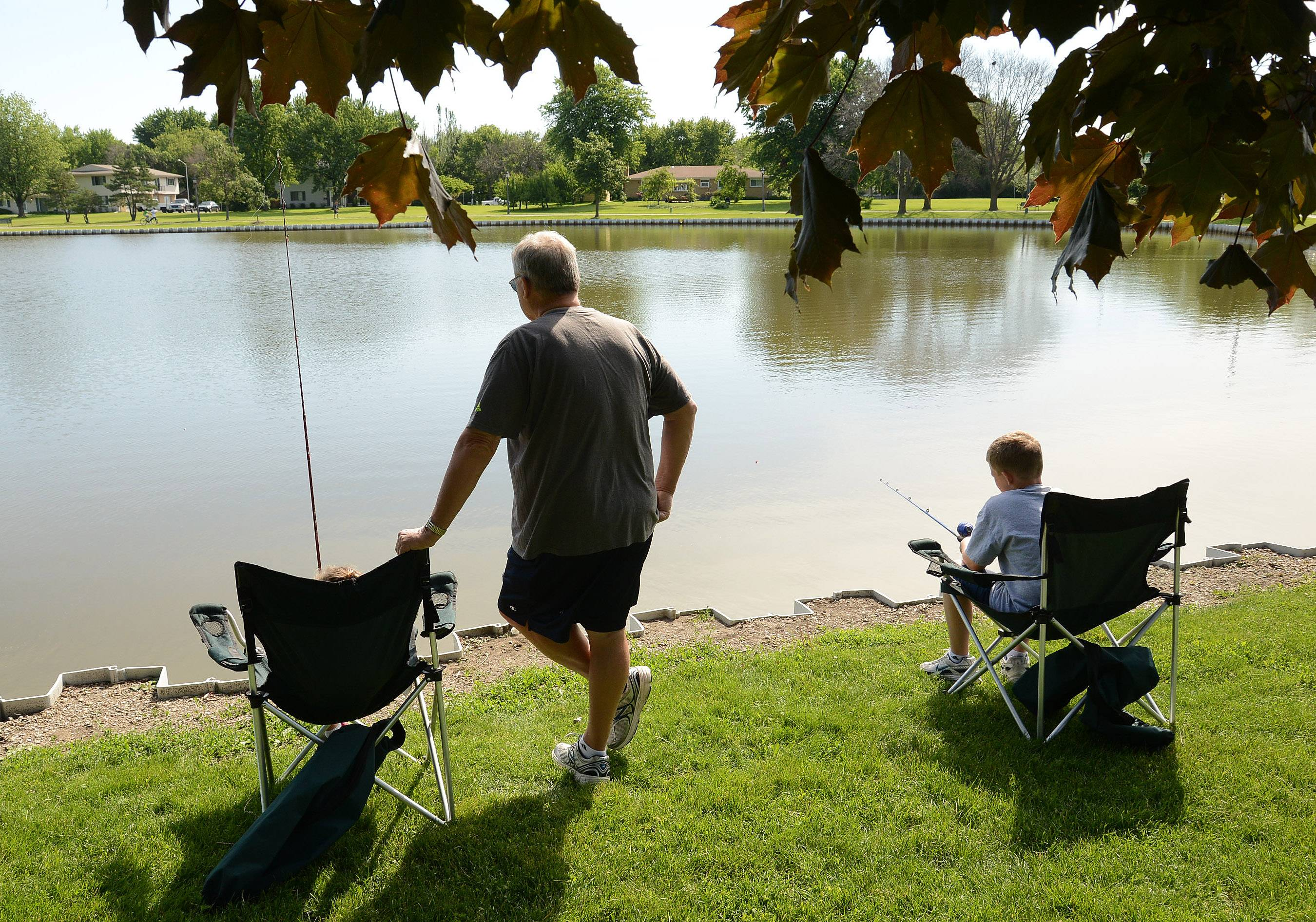 Brian Mores fishes with his grandchildren Kate Mores, left, and Hayden Mores, right, during Schaumburg Father's Day Weekend Fishing Derby at Volkening Lake.