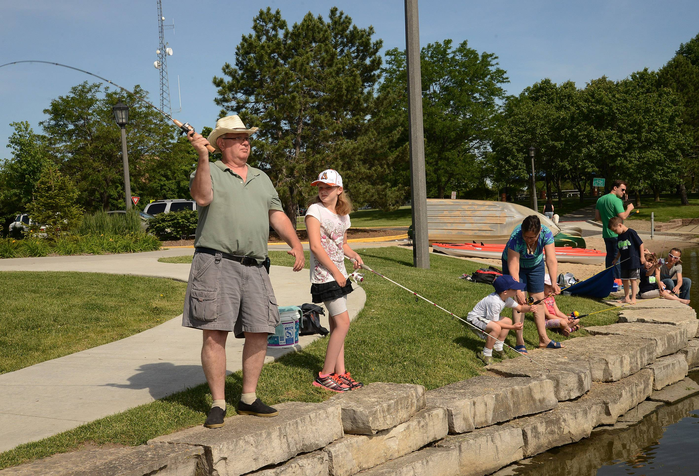 Jim Uchwat shows his granddaughter Brytni how to cast out a line during Schaumburg Father's Day Weekend Fishing Derby at Volkening Lake.