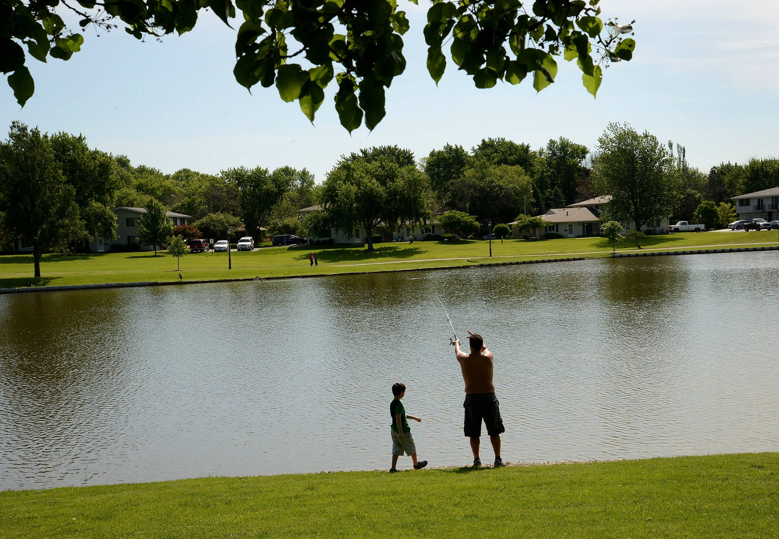 Mike Farr casts out a line for his son Maxwell during the Schaumburg Father's Day Weekend Fishing Derby at Volkening Lake.