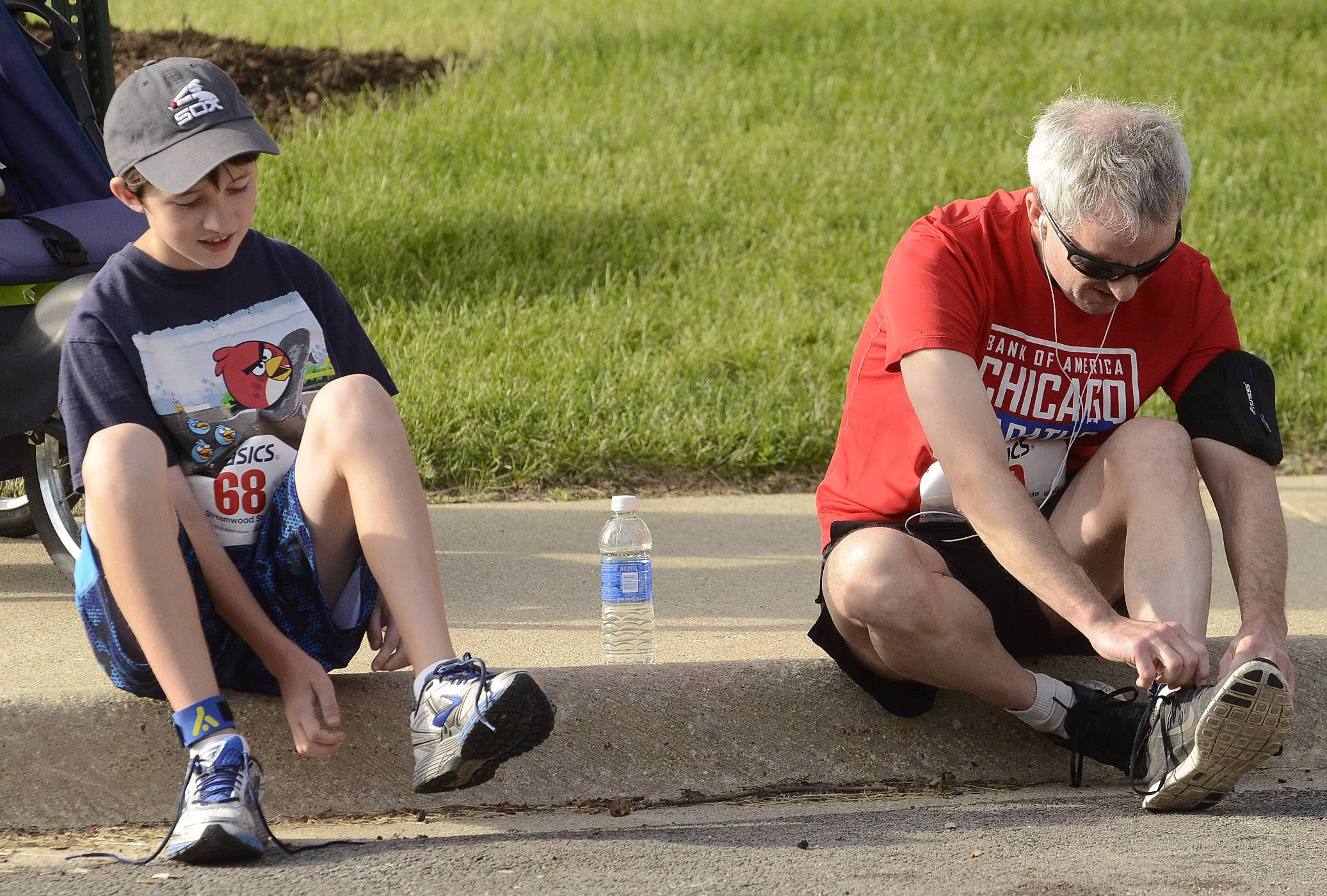 John Gulliford, 48, of Schaumburg, and his son Paul, 11, lace-up their shoes before the start of the Streamwood Stride 5K/10K/Fun Run Saturday morning at the Park Place Family Recreation Center. Gulliford has been running since the 1970s, and has run in eight marathons including Boston.