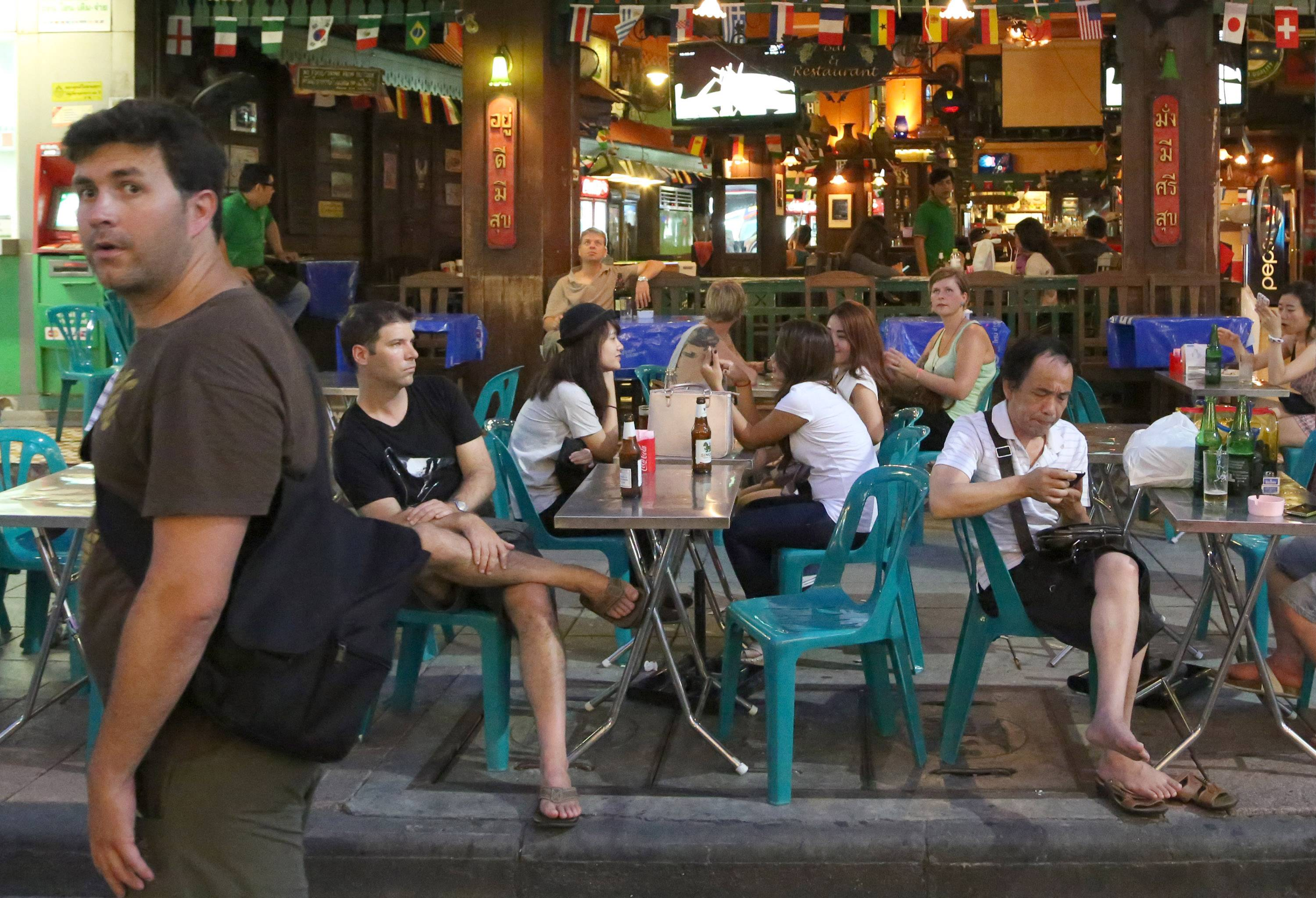 A tourist, left, walks past as others sit Saturday at a restaurant in Bangkok's Khaosan road, Thailand.