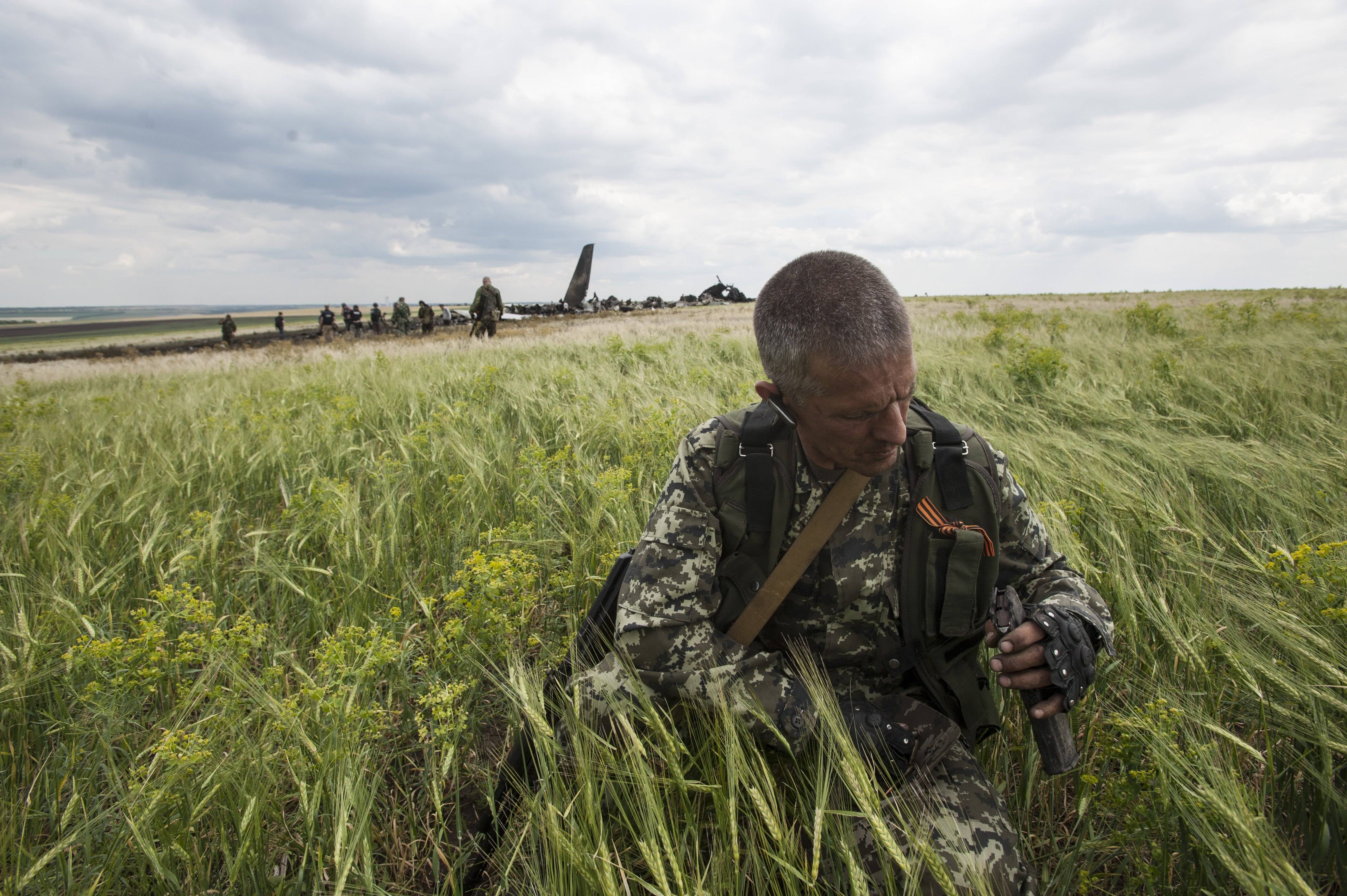 A pro-Russian fighter collects ammunition from the site of remnants of a downed Ukrainian army aircraft Il-76 at the airport near Luhansk, Ukraine, Saturday, June 14. Pro-Russian separatists shot down the military transport plane Saturday in the country's restive east, killing all 49 service personnel on board, Ukrainian officials said.