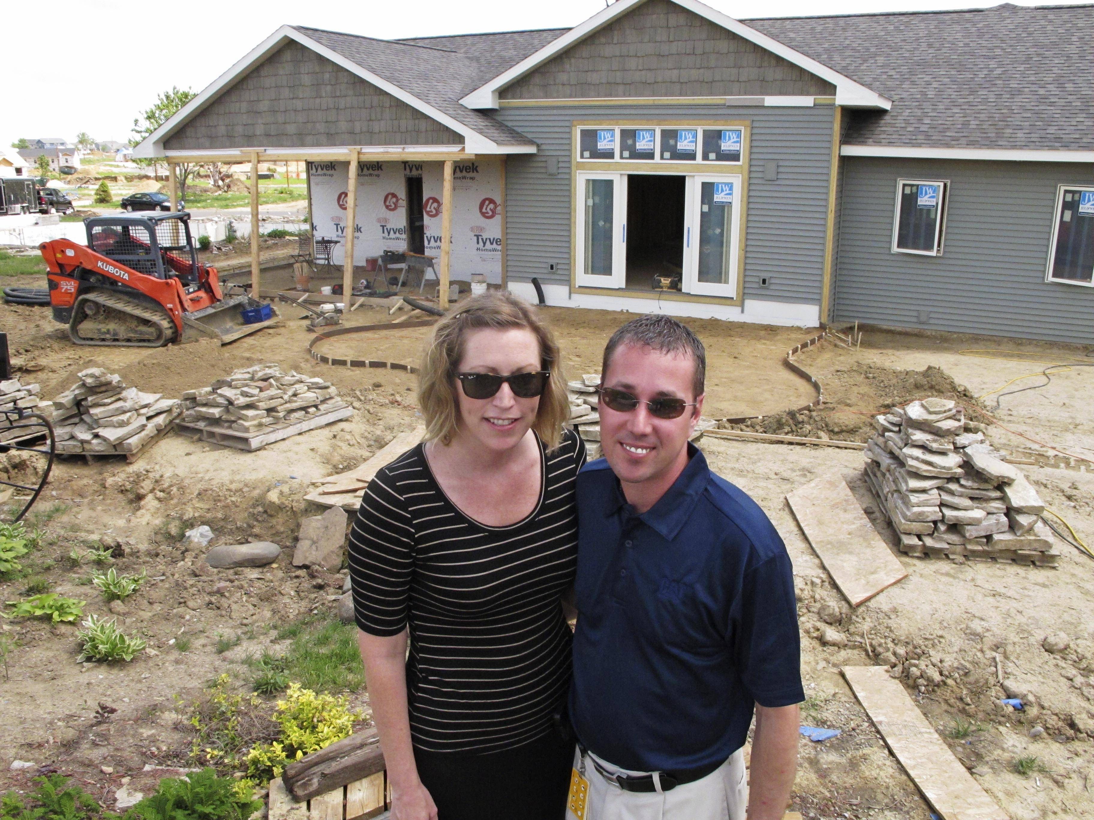 In this May 28 photo, Jamie and Daniel Cobb pose in the backyard of the their home, now being rebuilt, in Washington, Ill. The Cobbs had lived in their house less than a year when it was destroyed by a tornado in November 2013. The couple expect to be able to move back in within a few months.