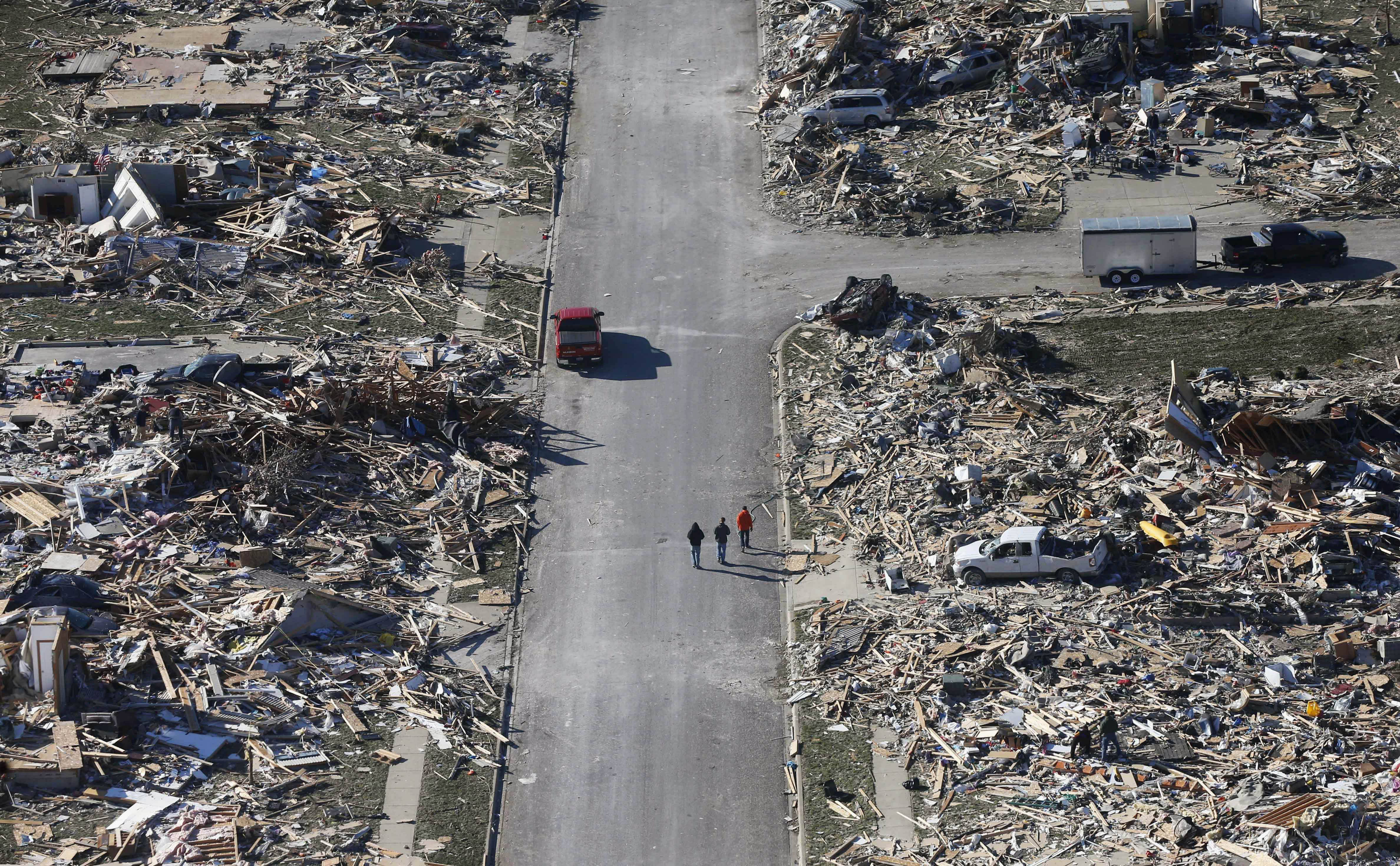 This Monday, Nov. 18, 2013, aerial file photo shows people walking down a street where homes once stood that were destroyed by a tornado that hit the western Illinois town of Washington. Mayor Gary Manier said the city has issued more than 600 building permits for the more than 1,000 badly damaged or destroyed homes. But construction was slowed by the harsh winter and for many is just beginning.