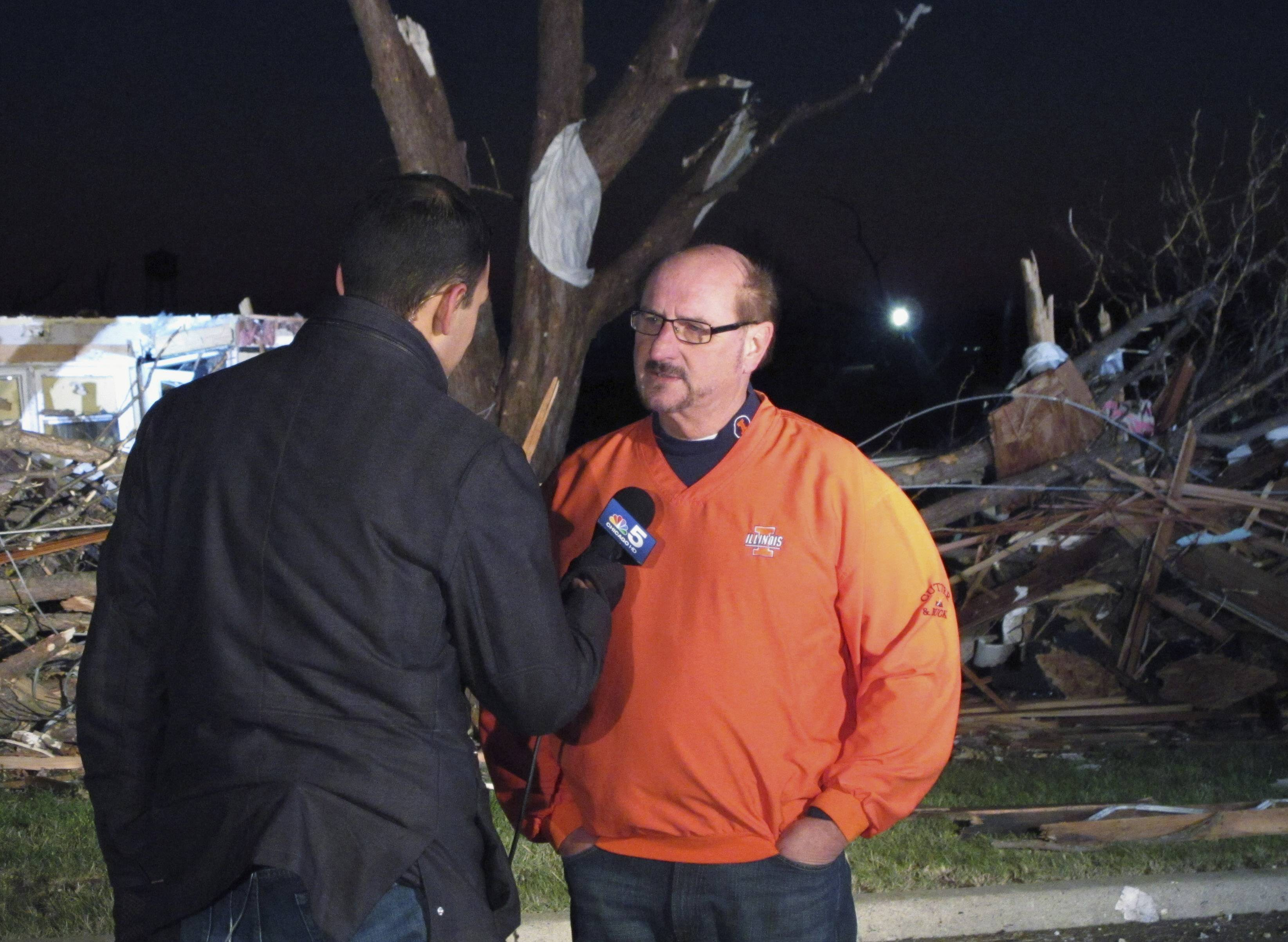 In this Nov. 18, 2013, photo, Gary Manier, right, the mayor of Washington, Ill., talks with a reporter in front of a row of homes leveled by a tornado the day before. Manier said the city has issued more than 600 building permits for the more than 1,000 badly damaged or destroyed homes. But construction was slowed by the harsh winter and for many is just beginning.
