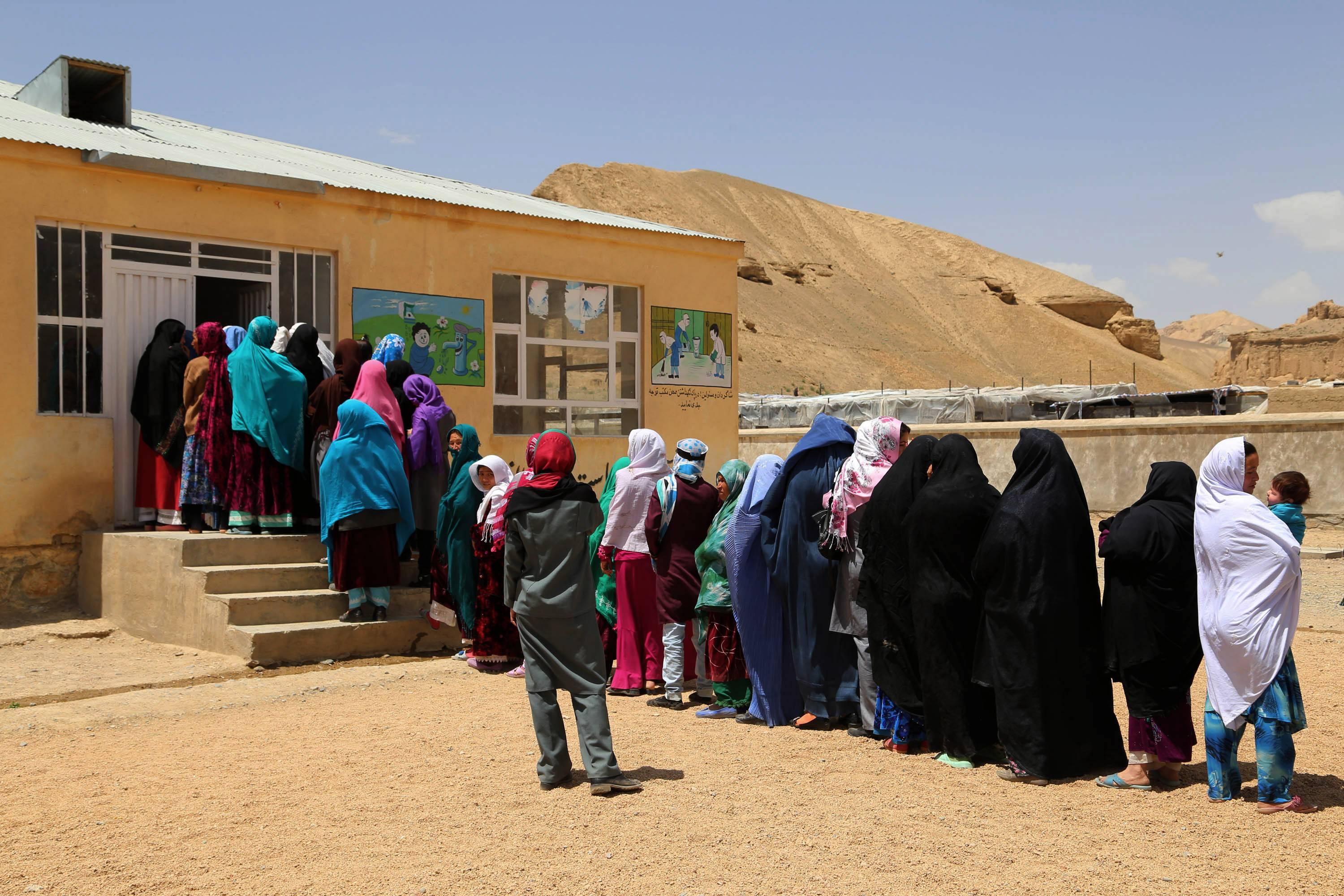 Afghan women line up to cast their votes, outside a polling station in Bamiyan, Afghanistan, Saturday, June 14. Despite Taliban threats of violence, many Afghans vow to cast ballots in Saturday's presidential runoff vote with hopes that whoever replaces Hamid Karzai will be able to provide security and stability after international forces wind down their combat mission at the end of this year.