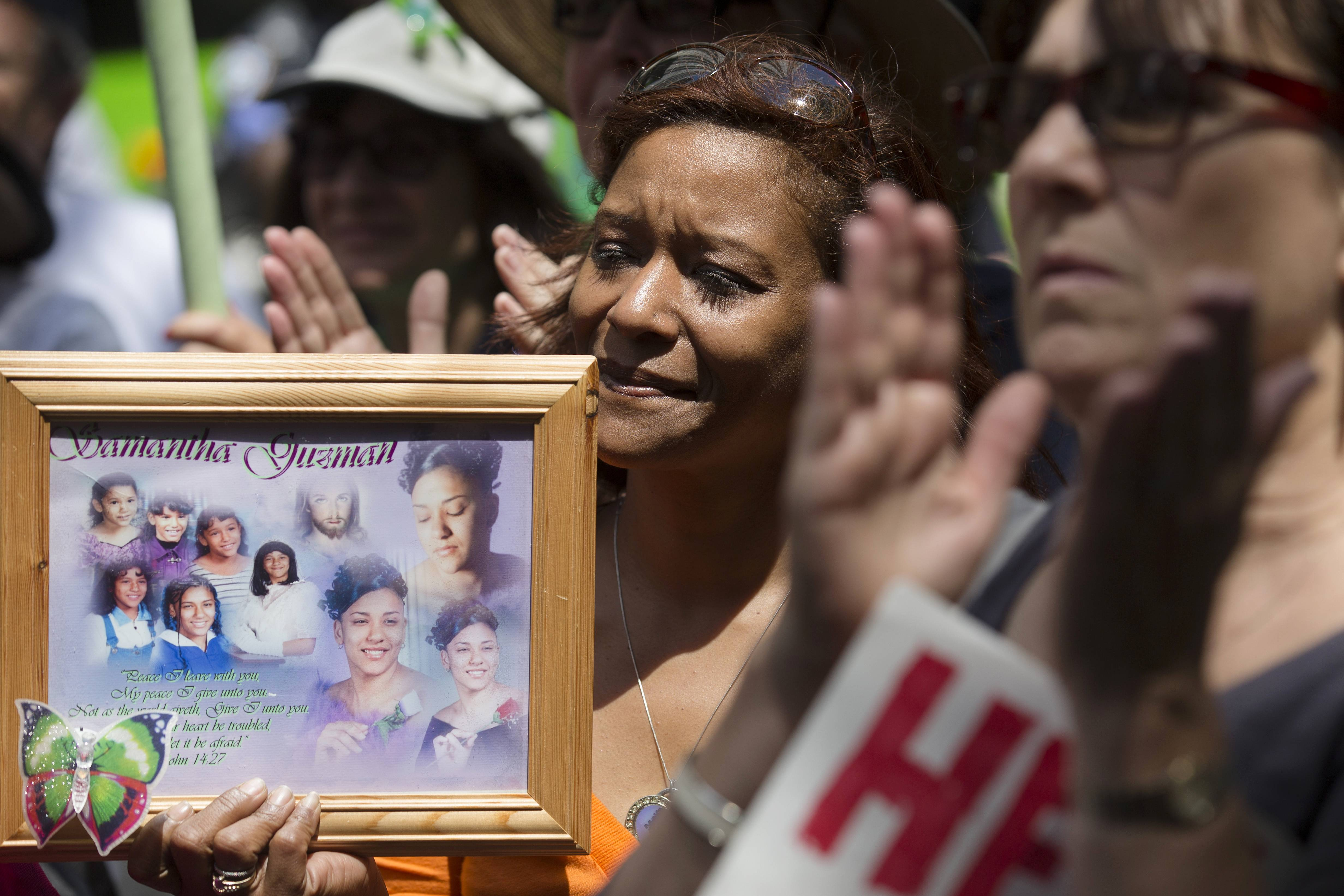 Diana Rodriguez, of Staten Island, holds a framed image of her daughter Samantha Guzman who was a victim of gun violence, at a rally outside city hall to call for tougher gun control laws, Saturday, June 14, in New York. The protest was underwritten by former New York Mayor Michael Bloomberg, one of the most visible gun control advocates in the U.S., and included relatives of some of those slain in the 2012 shooting rampage at Sandy Hook Elementary School in Newtown, Conn.