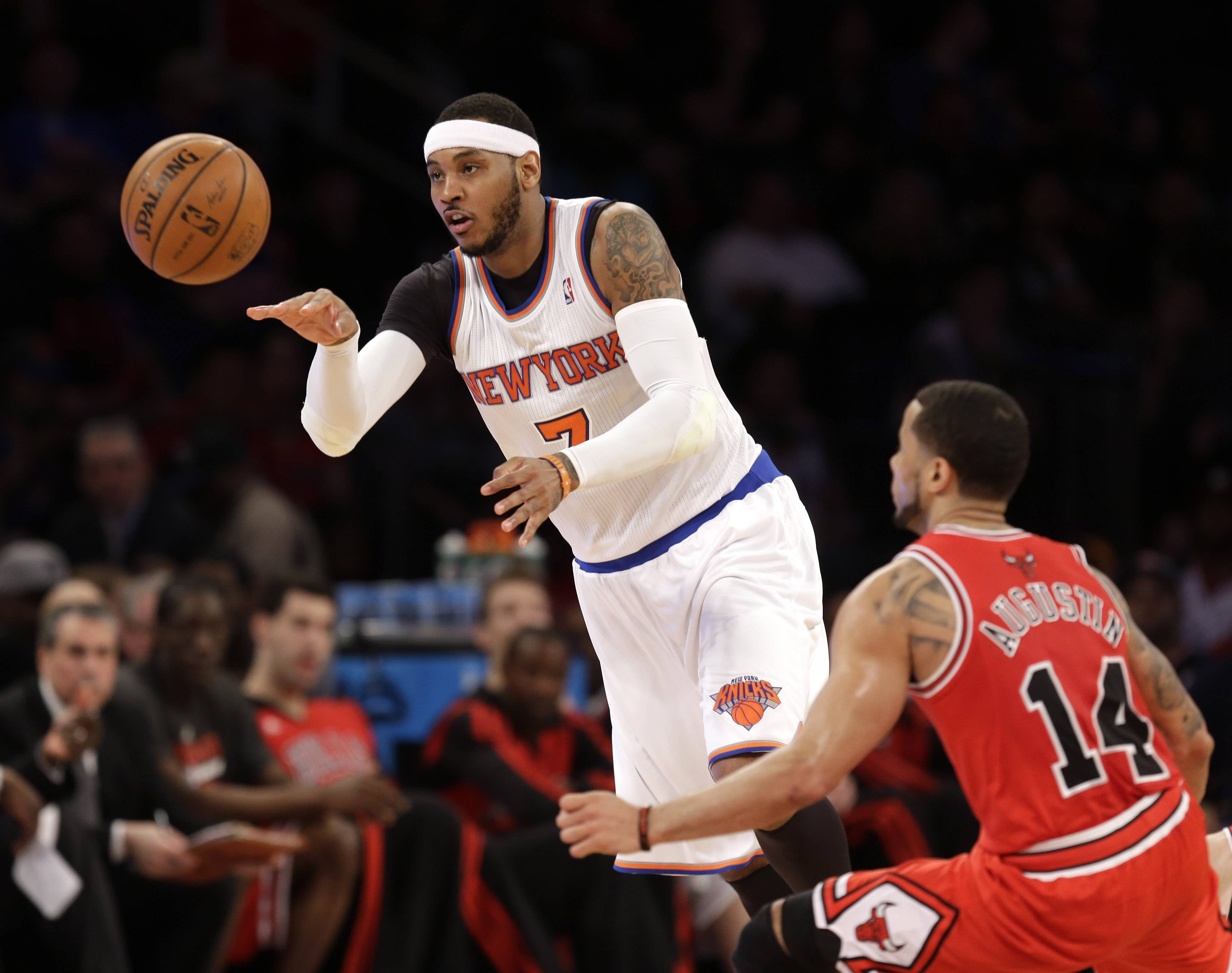New York Knicks' Carmelo Anthony, left, passes the ball past Chicago Bulls' D.J. Augustin during the first half of the NBA basketball game, Sunday, April 13, 2014 in New York. The Knicks defeated the Bulls 100-89.