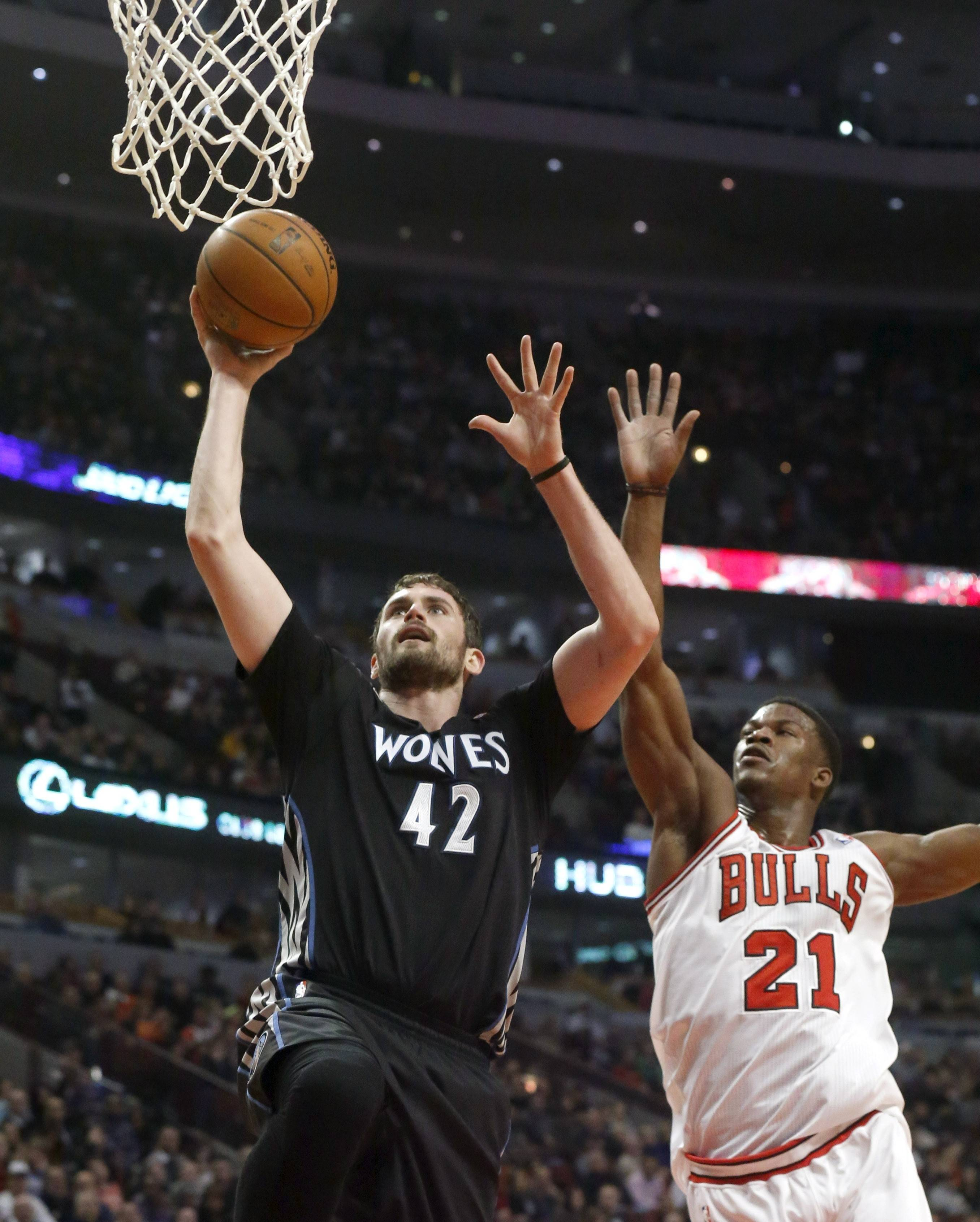 Minnesota Timberwolves forward Kevin Love (42) scores past Chicago Bulls guard Jimmy Butler (21) during the first half of an NBA basketball game, Monday, Jan. 27, 2014, in Chicago.