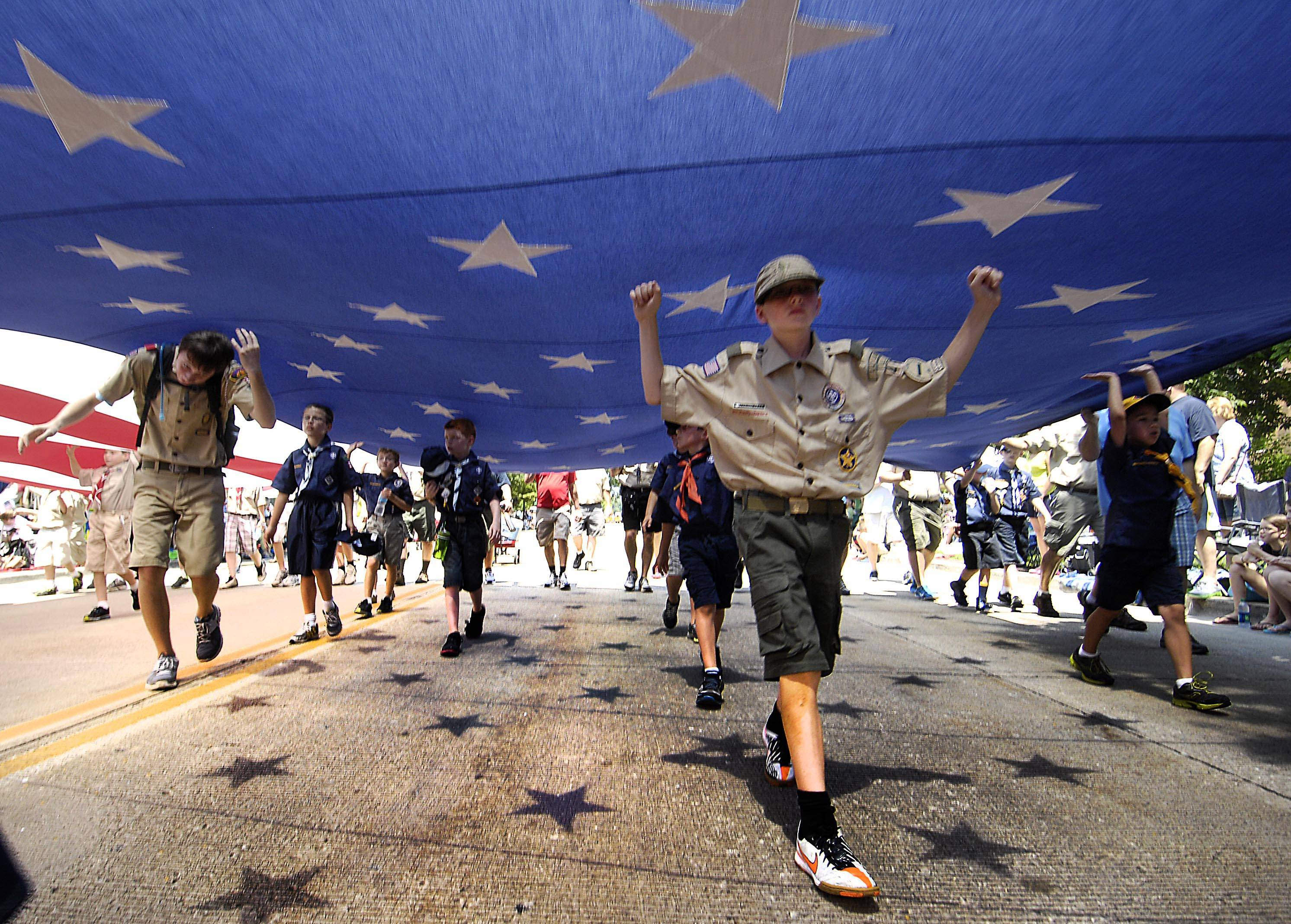 Dozens of Boy Scouts from local troops carry a huge American Flag, on loan from the Aurora Fire Department, at last year's Swedish Days parade in Geneva.