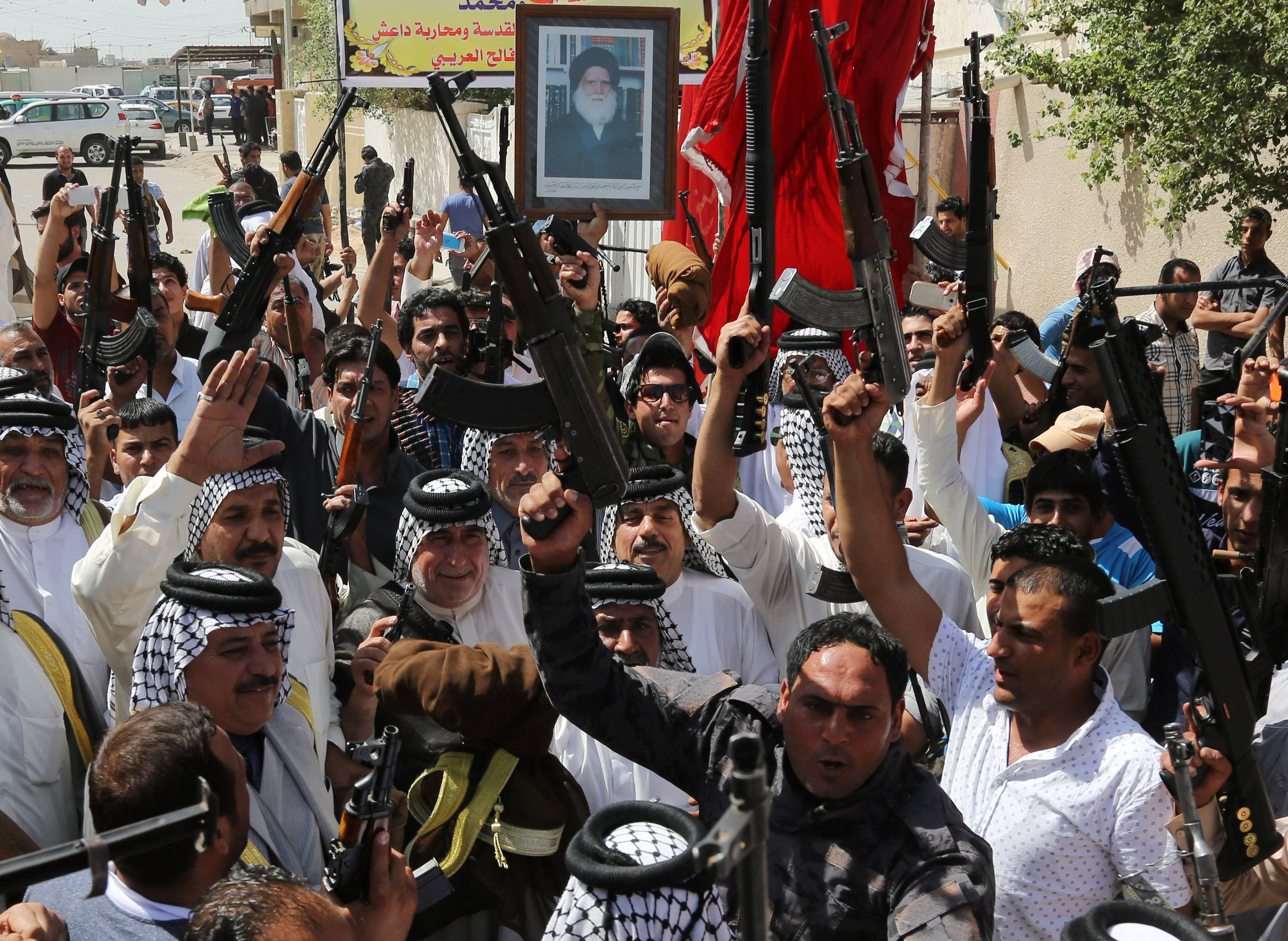 Iraqi Shiite tribal fighters raise their weapons and chant slogans against the al-Qaida-inspired Islamic State of Iraq and the Levant (ISIL) in Baghdad's Sadr city, Iraq. Emboldened by a call to arms by the top Shiite cleric, Iranian-backed militias have moved quickly to the center of Iraq's political landscape.