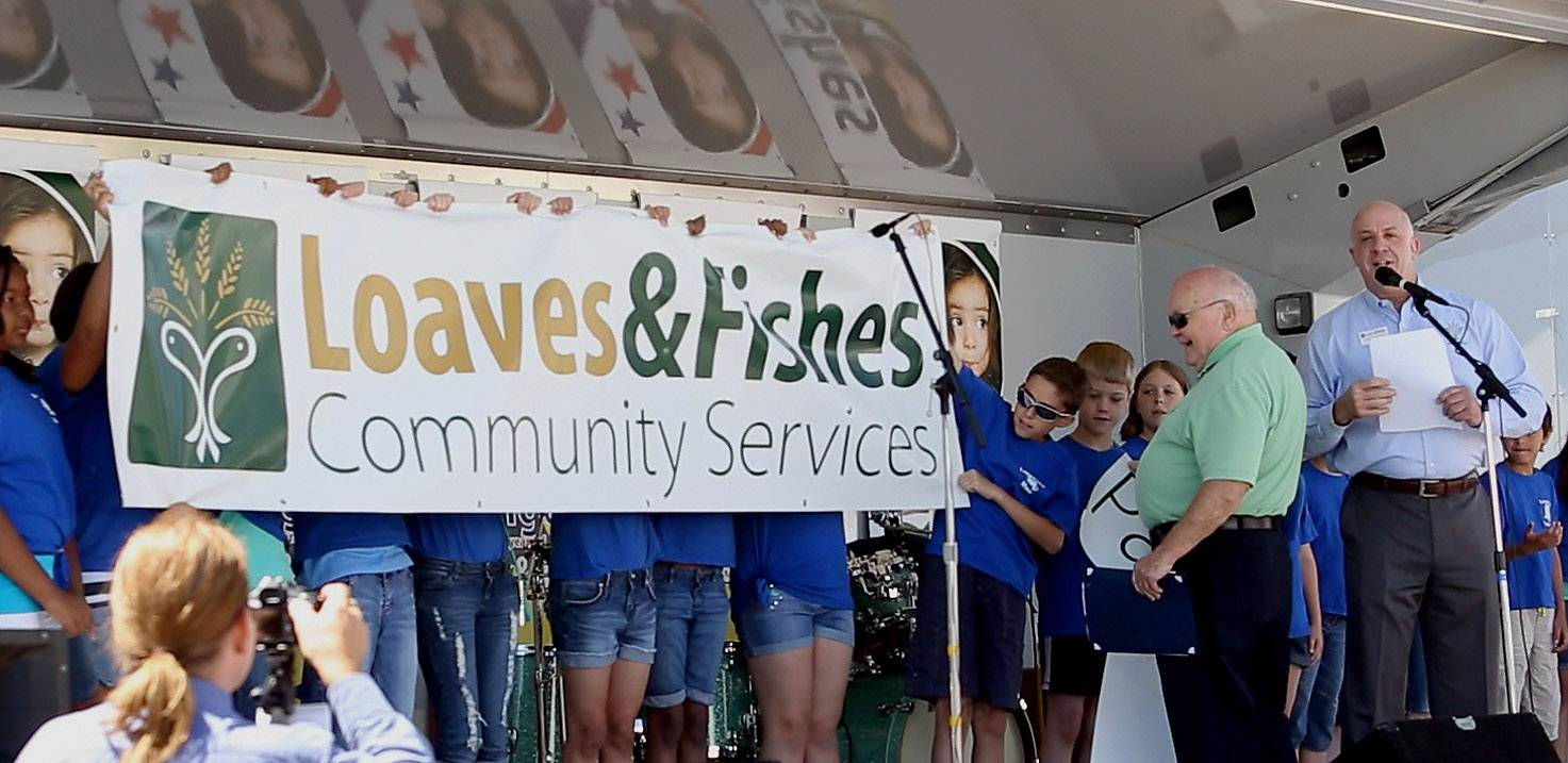Naperville Mayor George Pradel unveils the new name of the city's longtime food pantry, which now is called Loaves & Fishes Community Services. The 30-year-old organization announced its new name Friday during the seventh annual Day Without Hunger festival.