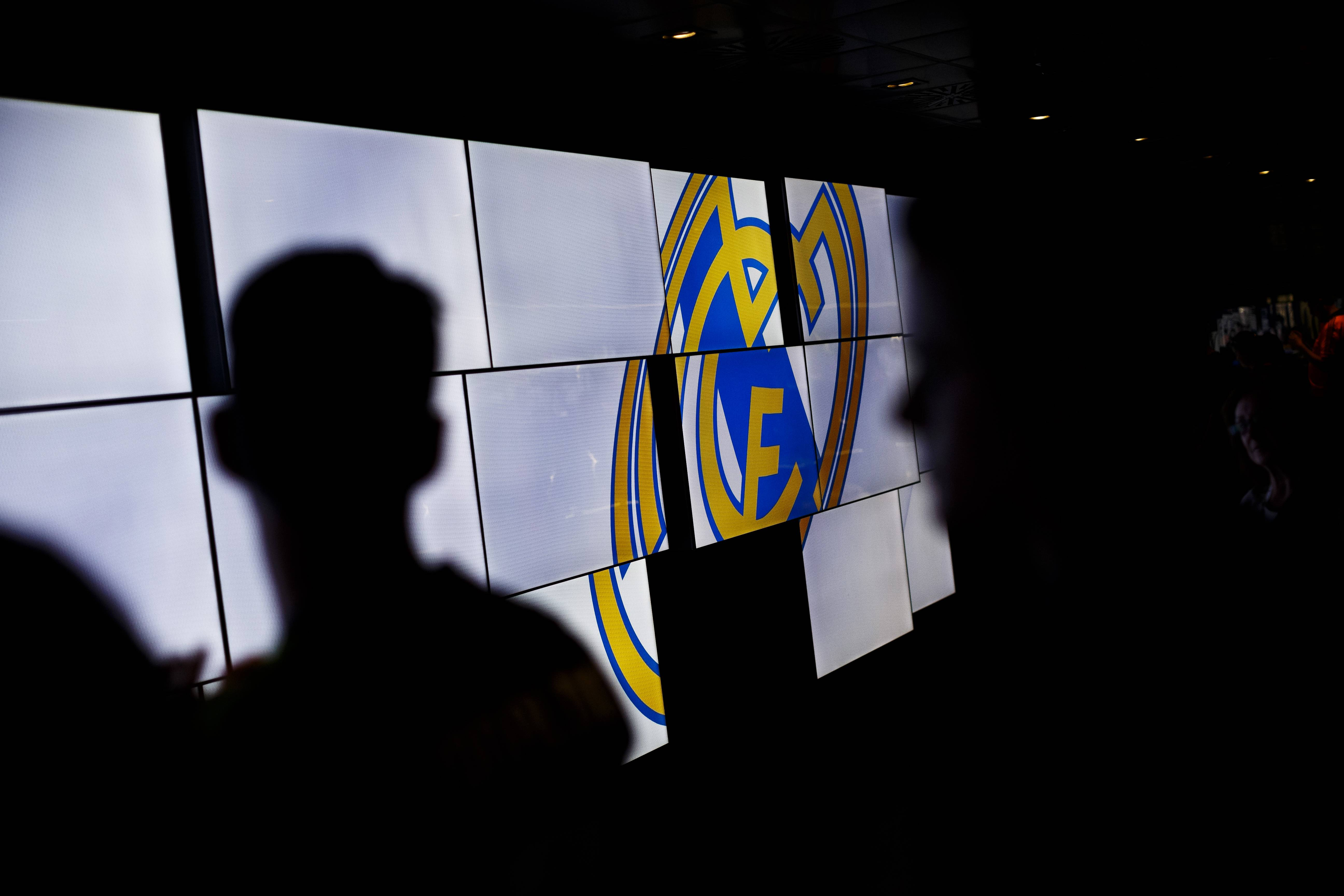 Real Madrid's supporters are backlighted by screens displaying the Real Madrid team emblem on the trophies gallery of the Santiago Bernabeu stadium in Madrid, Spain. The European Union is investigating whether government loan guarantees for seven soccer clubs violate EU competition law.