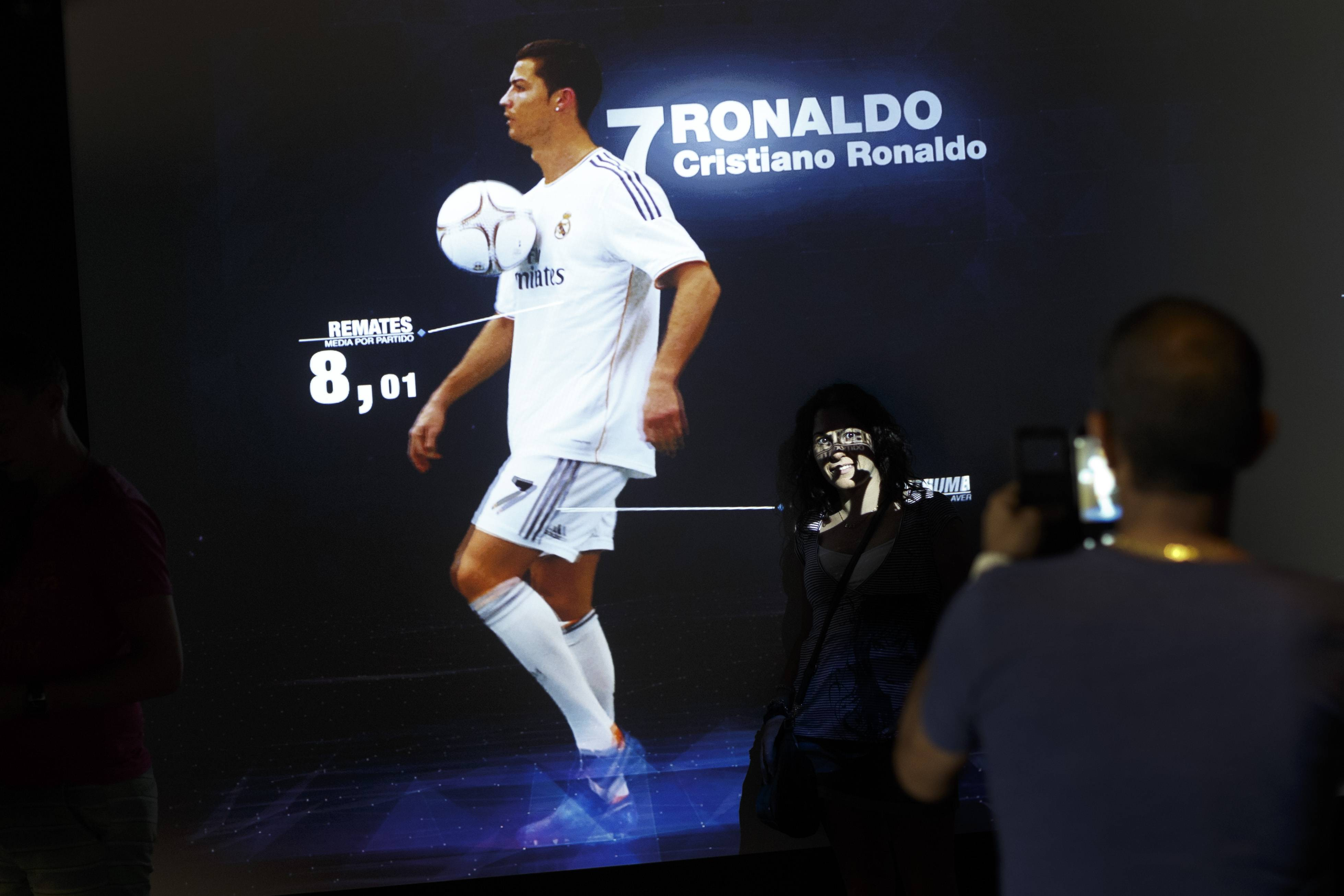A Real Madrid's supporter takes a snapshot of a screen displaying the profile of Real Madrid's player Cristiano Ronaldo from Portugal at the museum of the Santiago Bernabeu stadium in Madrid, Spain.