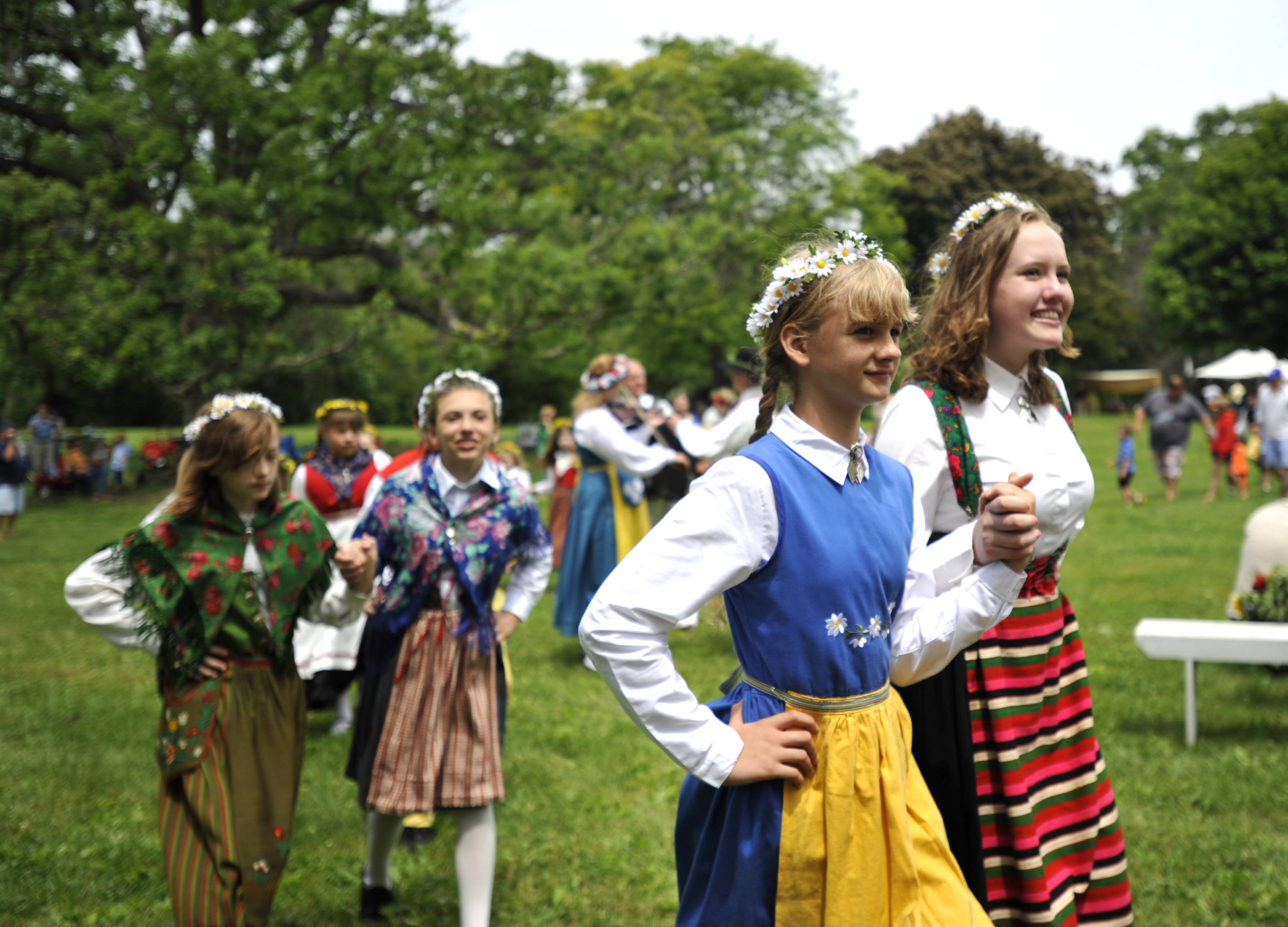 Louisa Olsen, 11, left, of Aurora and Lucy Smith, 14, of Geneva, walk in the procession Sunday before the Maypole dancing at the 104th annual Swedish Day Midsommar Festival in Geneva.