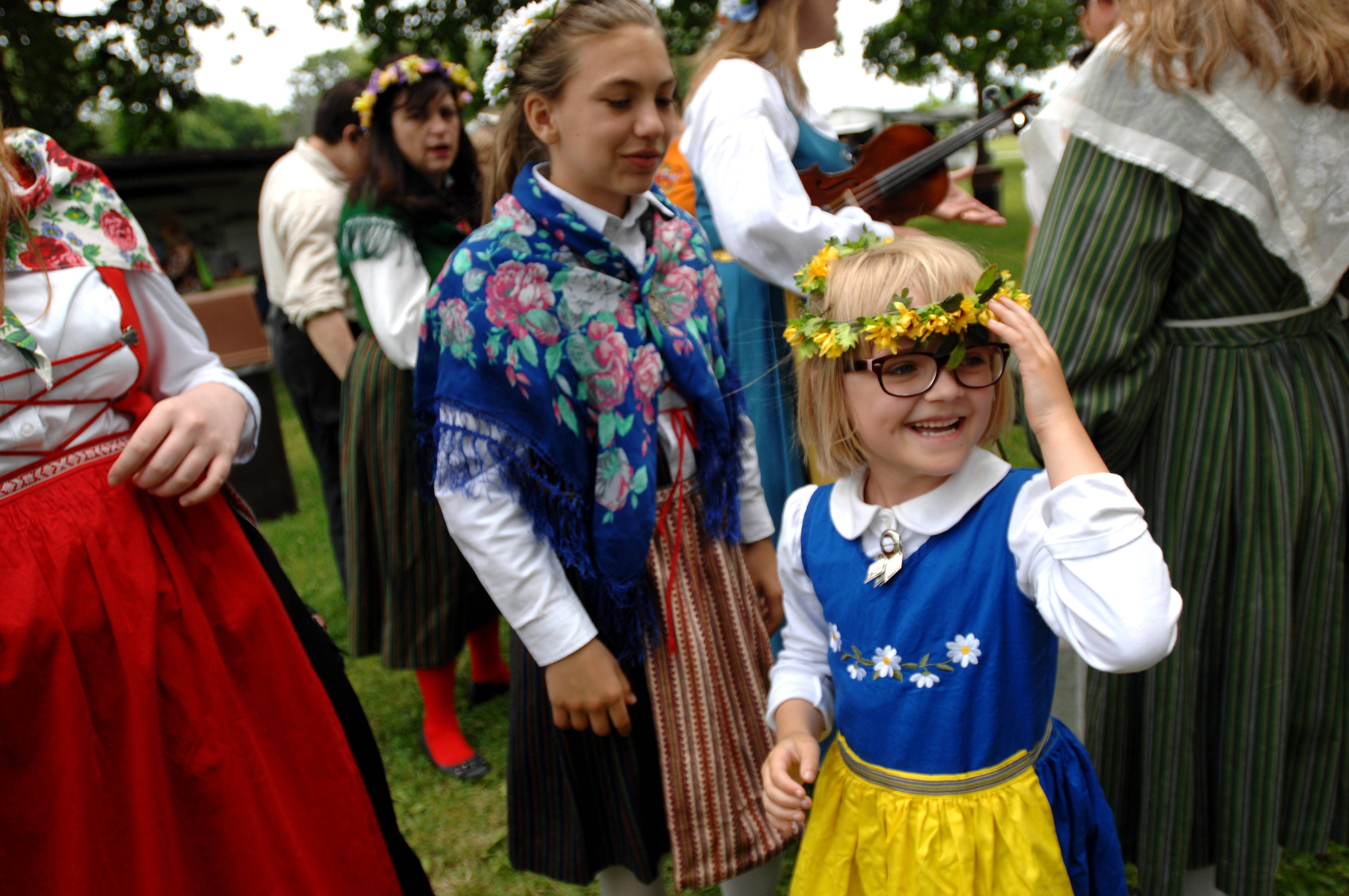 Kyley Cahill, 7, of Sycamore adjusts her flower crown after greeting her friend Sydney Poss, 11, of North Aurora Sunday at the 104th annual Swedish Day Midsommar Festival in Geneva. Cahill and Poss are members of the Swedish American Children's Choir, the largest Swedish children's choir in the Midwest, with 32 members ages 4-16.