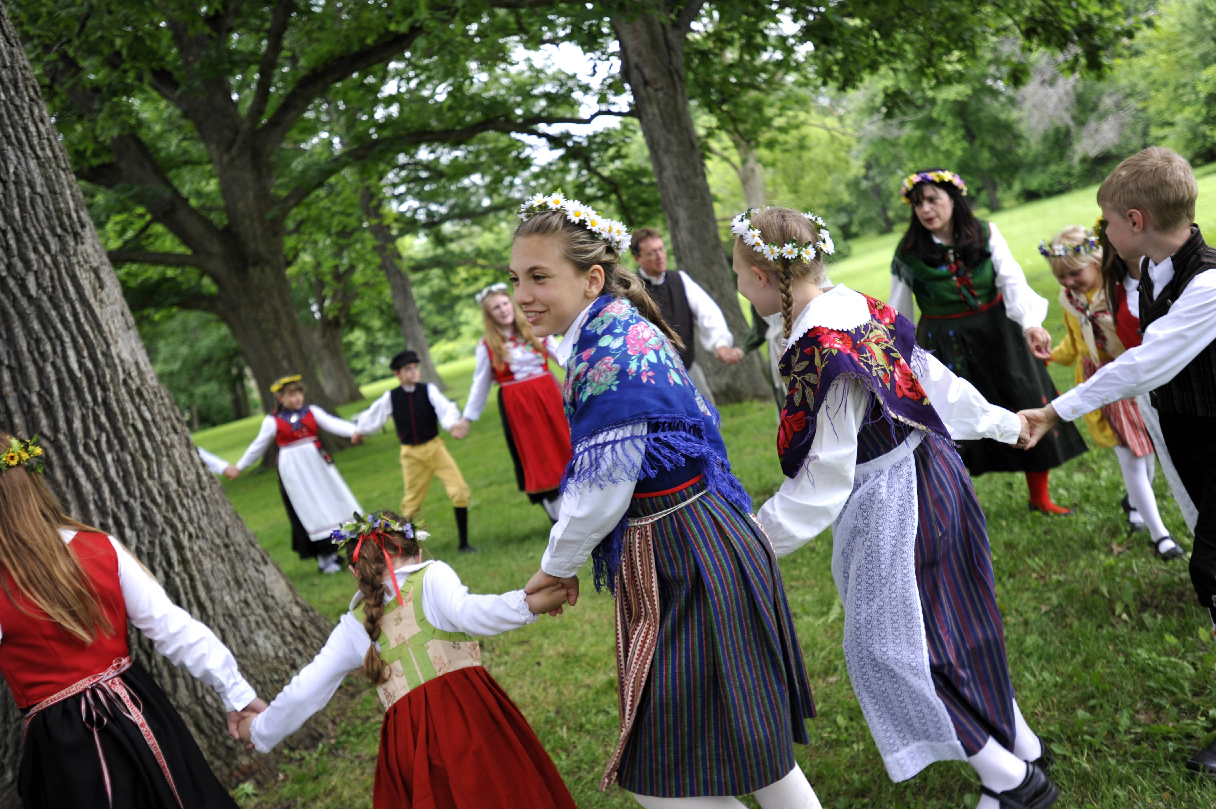 Sydney Poss, 11, of North Aurora, dances around a tree Sunday with other members of the Swedish American Children's Choir during the Maypole dancing at the 104th annual Swedish Day Midsommar Festival in Geneva.