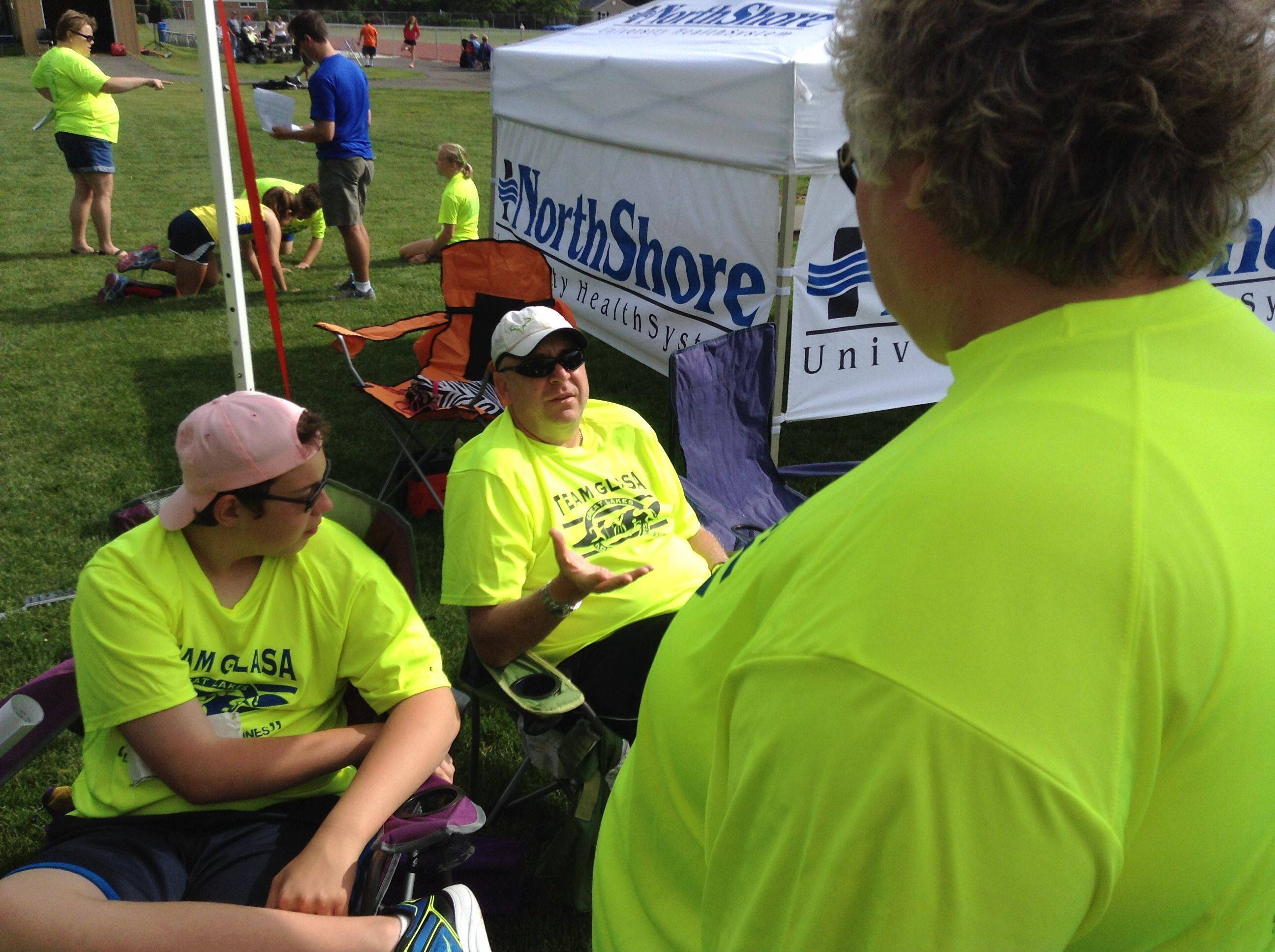 Athlete Brian Nelson, left, and Darren Bolton, parent of athlete Sarah Bolton, chat with Brian's mom Ginnie, at the Great Lakes Adaptive Sports Association regional games at Lake Forest High School on Sunday.