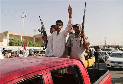 Iraqi Shiite fighters deploy with their weapons in Basra, Iraq's second-largest city, 340 miles southeast of Baghdad, Iraq, Saturday.