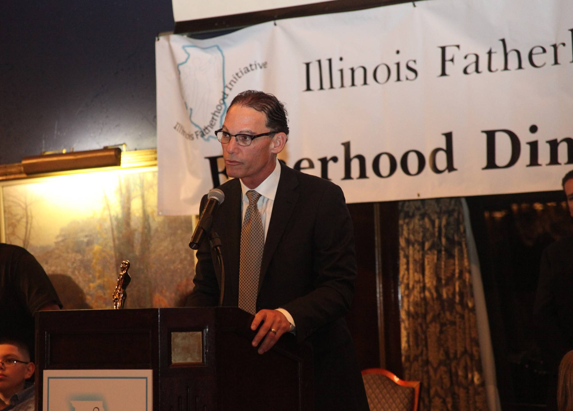 "Showing that life is more than football, Chicago Bears Coach Marc Trestman receives a ""Father of the Year"" award from the Illinois Fatherhood Initiative. He attended Wednesday evening's event with his wife and two daughters."