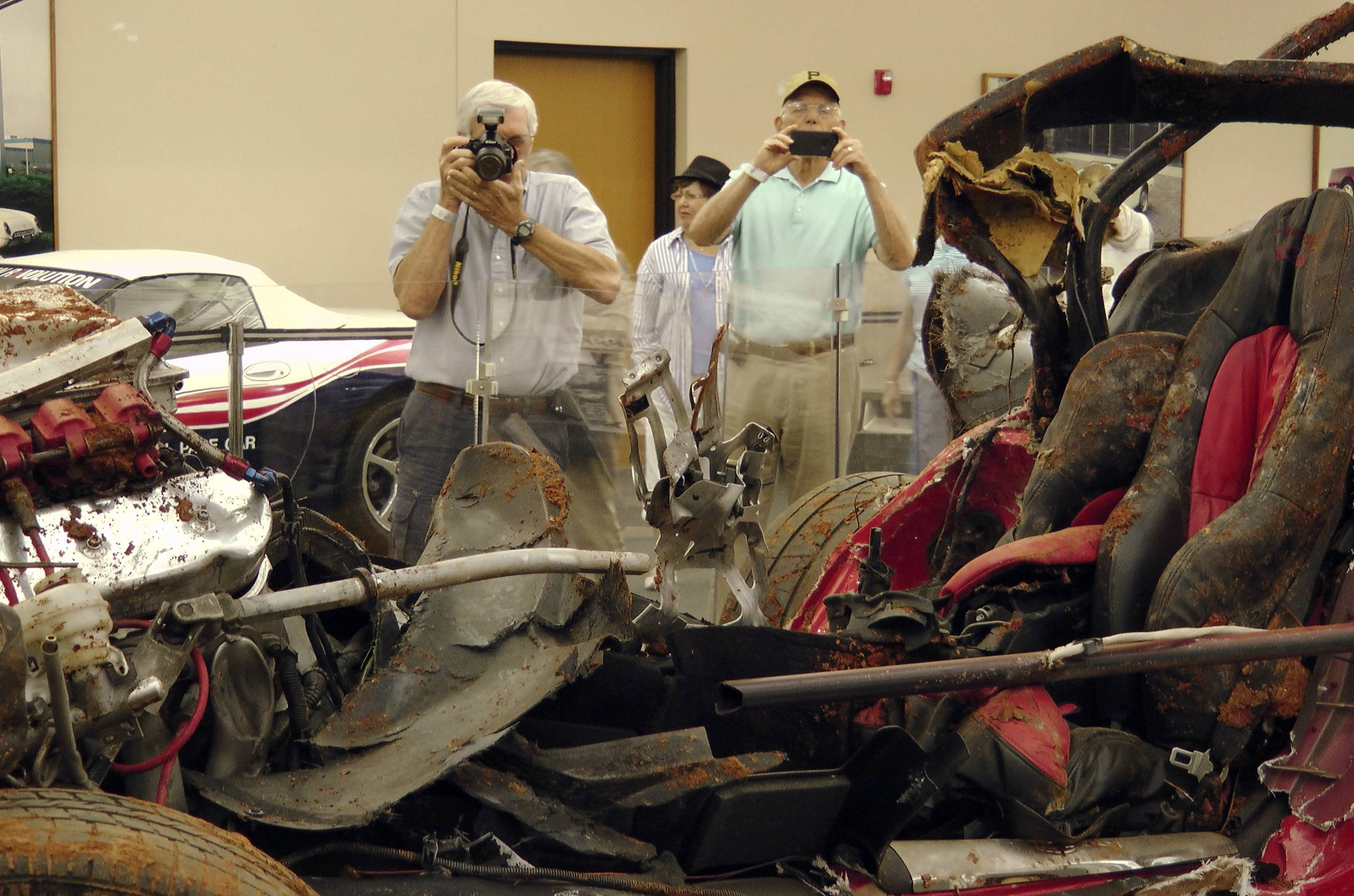 Lynn Jones, left, takes a photo of a 2001 Corvette that fell into a sinkhole at the National Corvette Museum in Bowling Green, Ky. Jones, from Collierville, Tenn., came to the museum to see the smashed cars and the sinkhole, which opened up and swallowed eight cars in February.