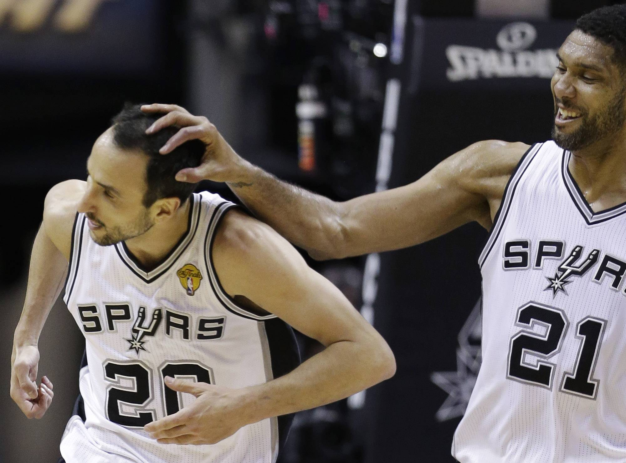 After dunking against the Miami Heat, San Antonio Spurs guard Manu Ginobili (20) is congratulated by forward Tim Duncan (21) during the first half in Game 5 of the NBA basketball finals on Sunday, June 15, 2014, in San Antonio.