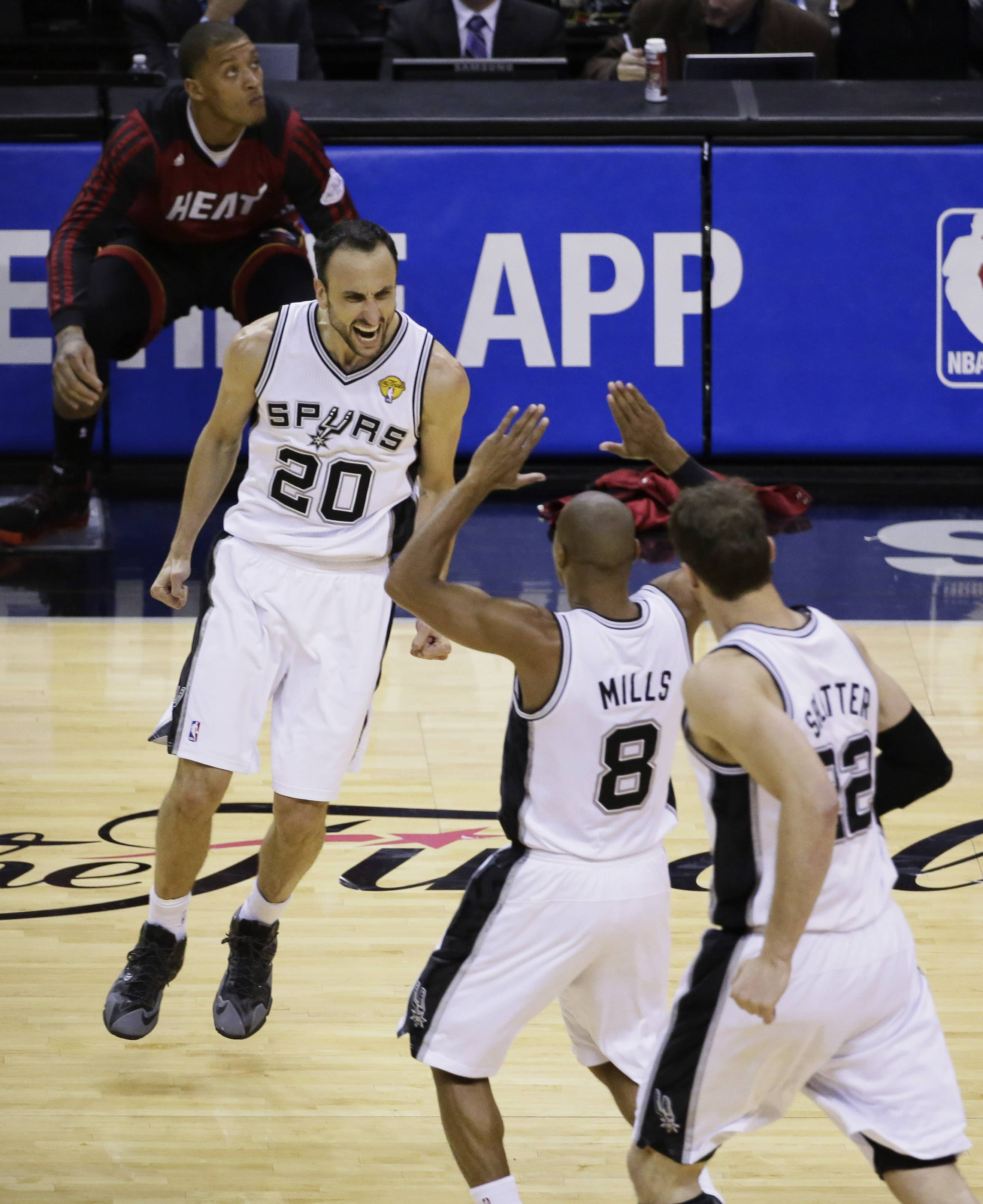 San Antonio Spurs guard Manu Ginobili (20), guard Patty Mills (8) and center Tiago Splitter (22) celebrate against the Miami Heat during the second half in Game 5 of the NBA basketball finals on Sunday, June 15, 2014, in San Antonio.
