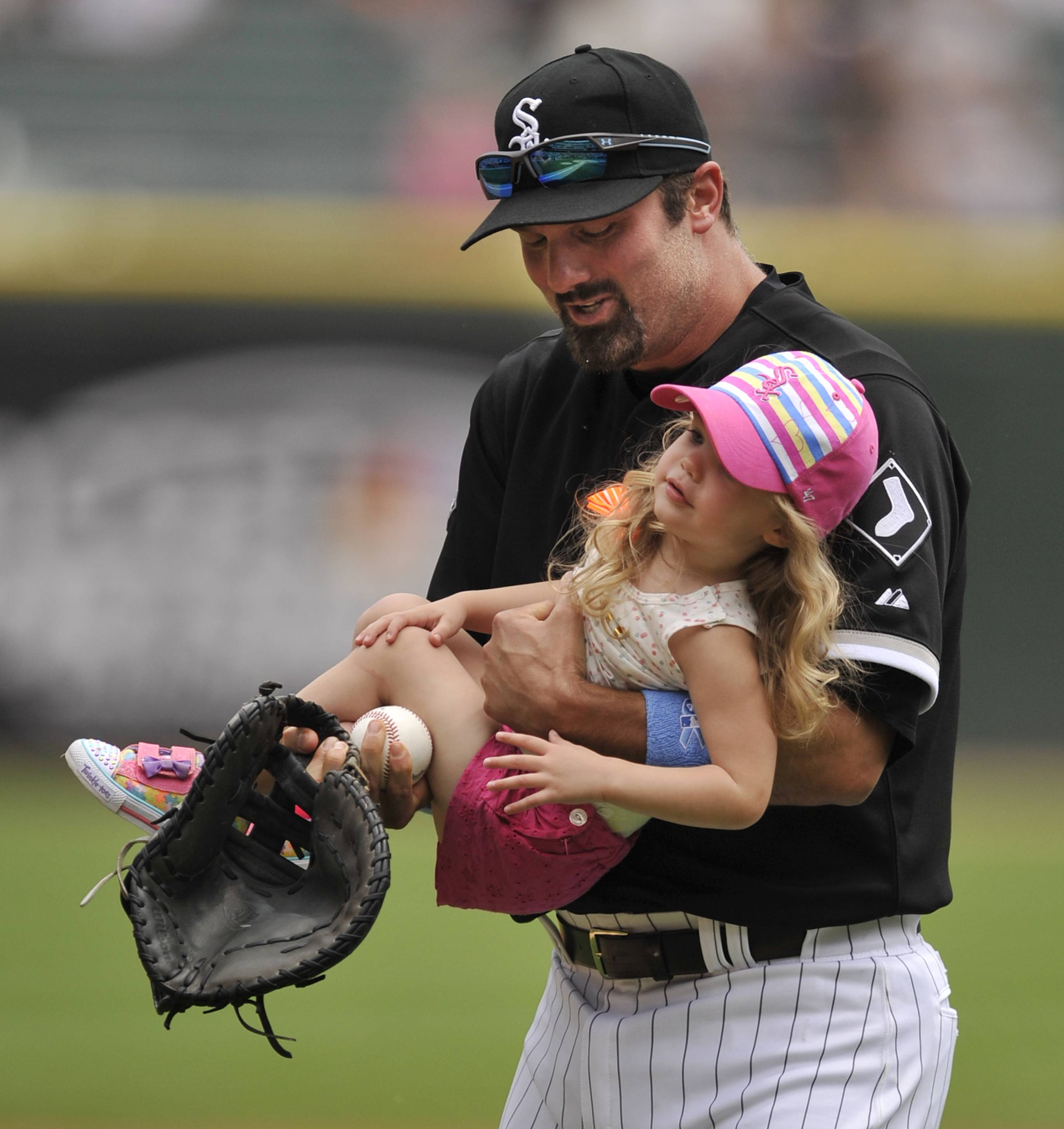 Amelia Konerko, 2, is carried off the field by her father, Chicago White Sox player Paul Konerko, after she threw out a ceremonial first pitch before a baseball game between the White Sox and the Kansas City Royals in Chicago, Sunday, June 15, 2014.
