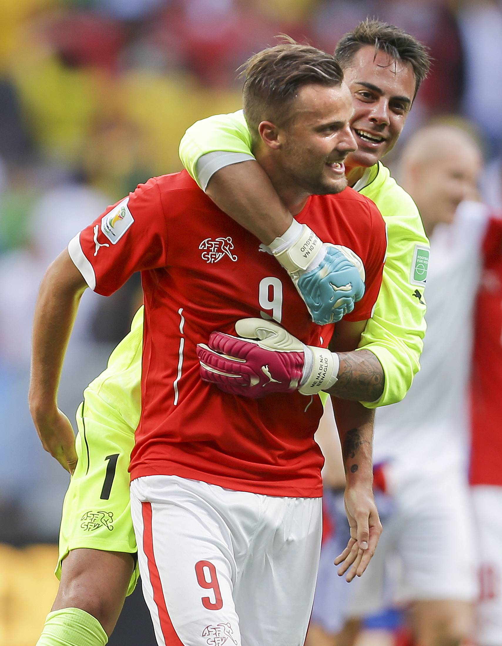 Switzerland's Haris Seferovic, front, and  goalkeeper Diego Benaglio celebrate after the group E World Cup soccer match between Switzerland and Ecuador at the Estadio Nacional in Brasilia, Brazil, Sunday, June 15, 2014. Switzerland won the match 2-1.