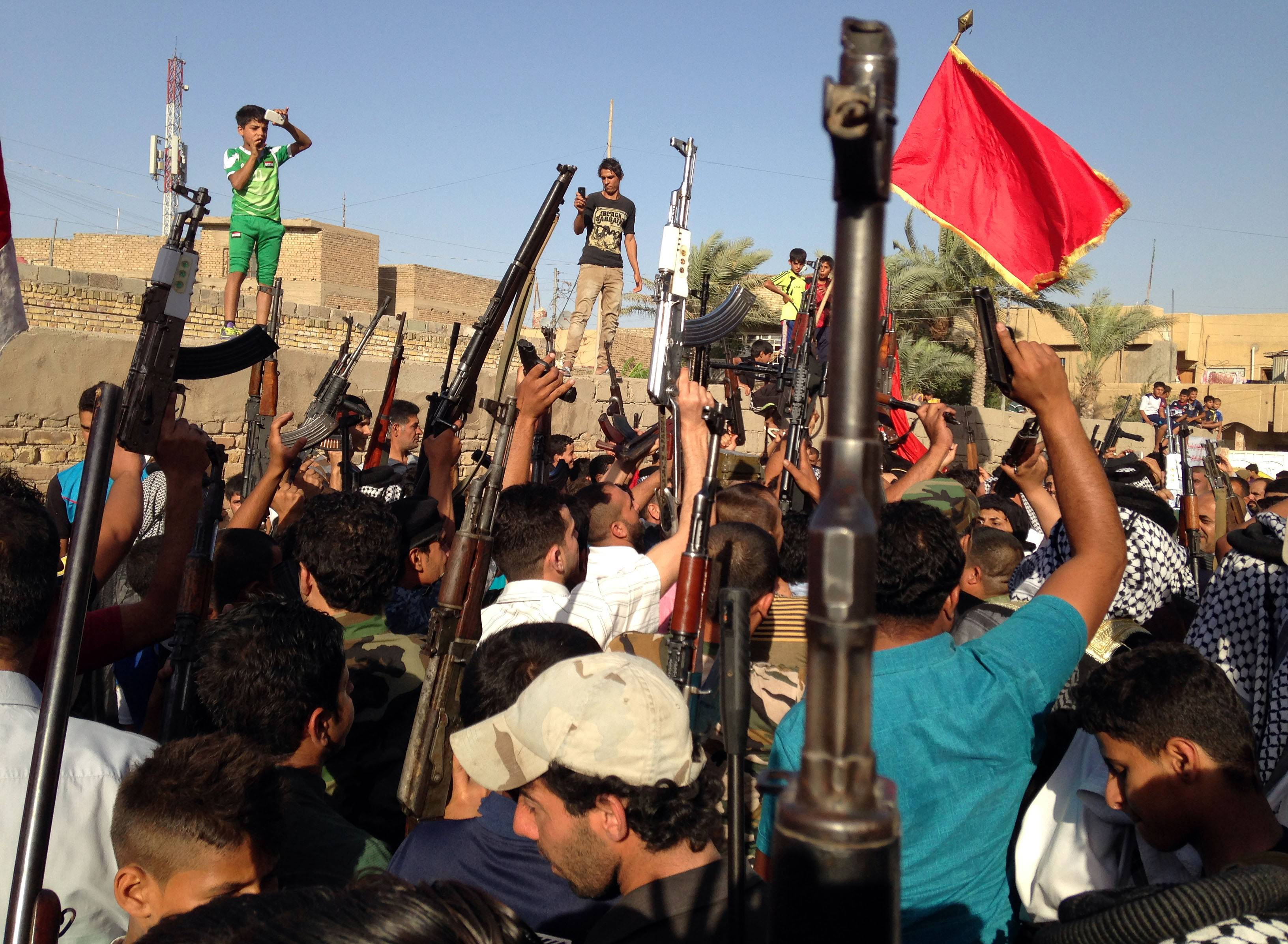 Shiite tribal fighters raise their weapons and chant slogans against the al-Qaida-inspired Islamic State of Iraq and the Levant (ISIL) in the east Baghdad neighborhood of Kamaliya, Iraq, Sunday, June 15, 2014. Emboldened by a call to arms by the top Shiite cleric, Iranian-backed militias have moved quickly to the center of Iraq's political landscape, spearheading what its Shiite majority sees as a fight for survival against Sunni militants who control of large swaths of territory north of Baghdad.