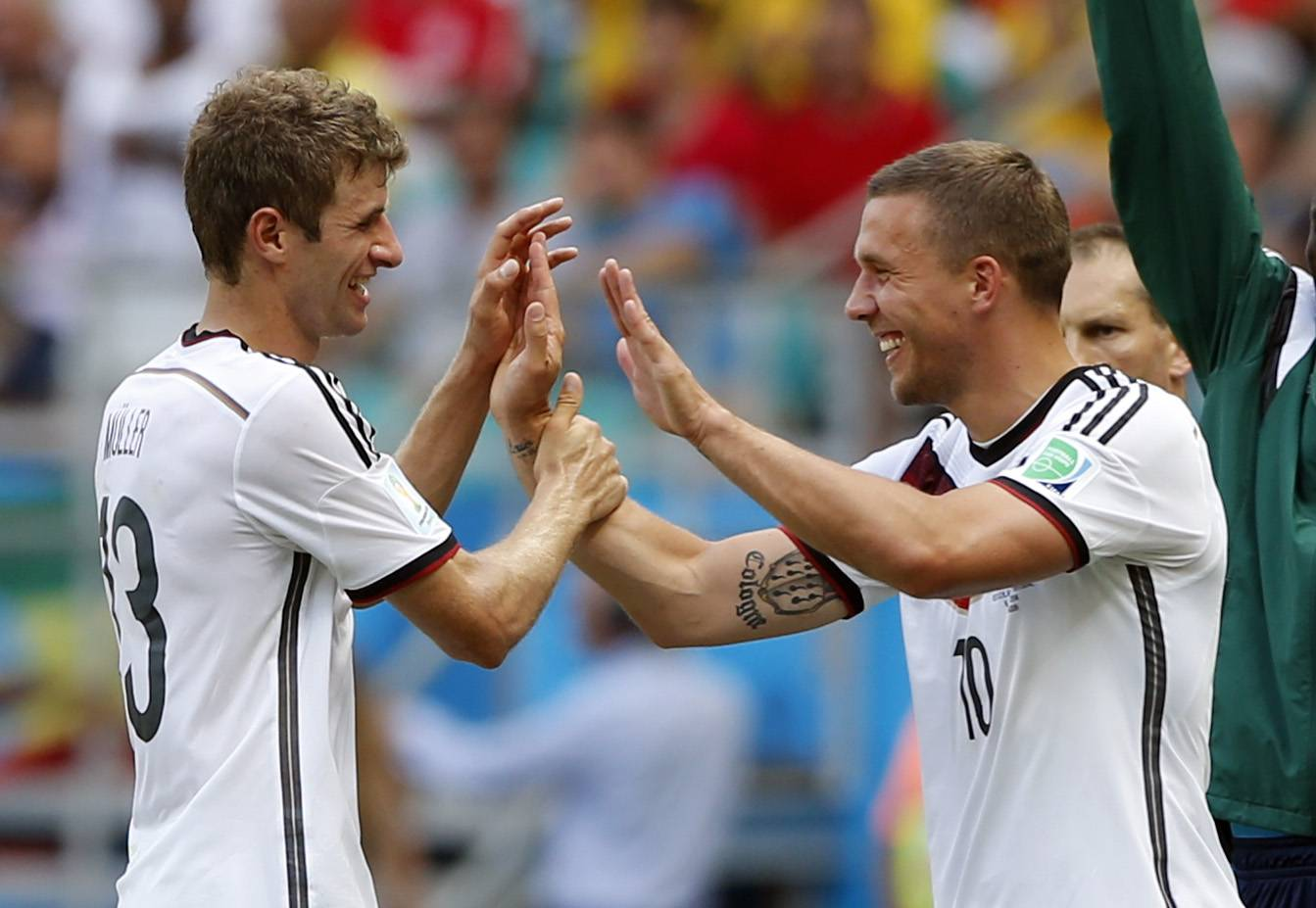 Germany's Thomas Mueller, left, is greeted by Lukas Podolski after being substituted after scoring a hat-trick during the World Cup soccer match between Germany and Portugal in Salvador, Brazil on Monday.