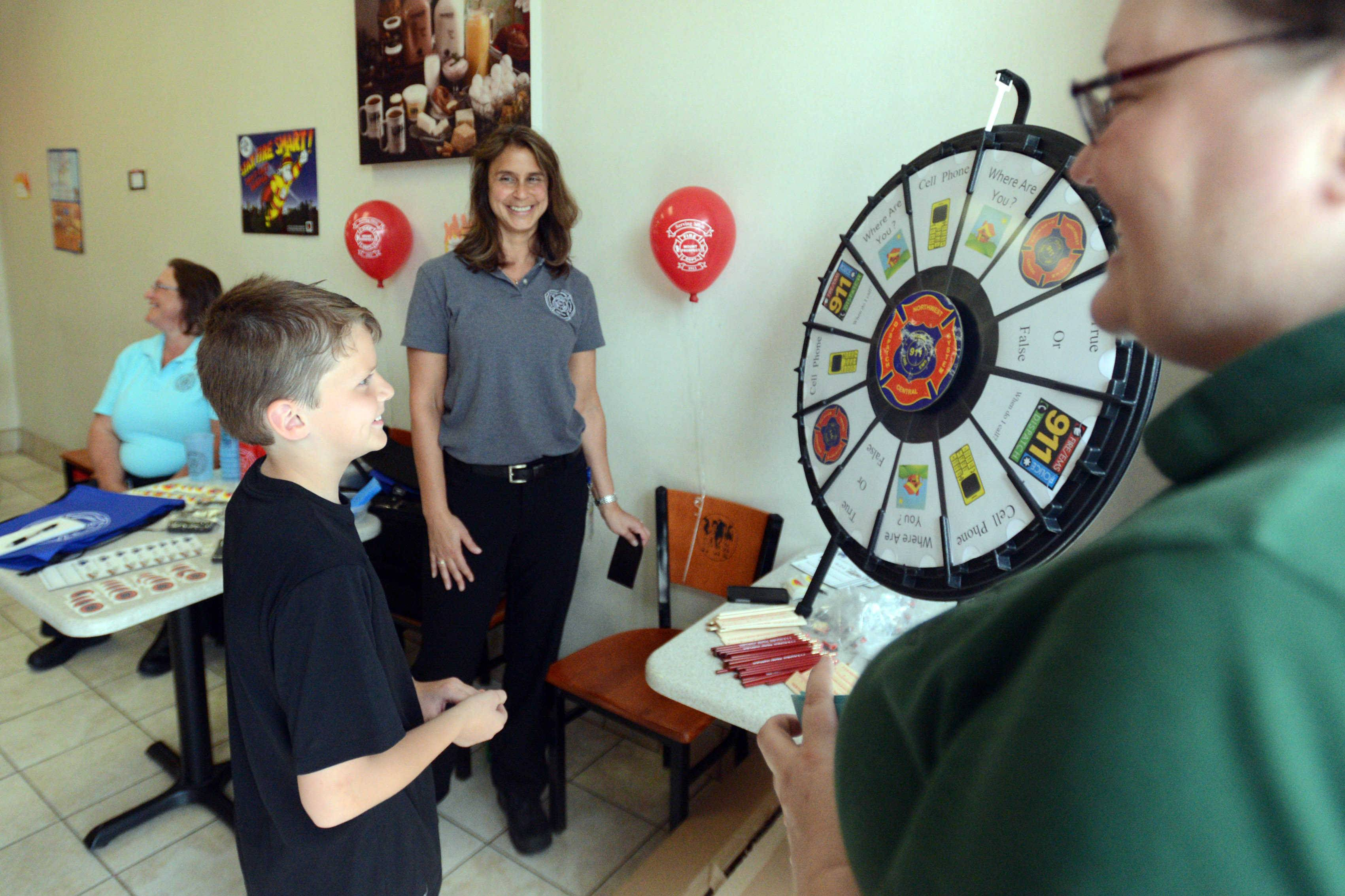 Mark Merrill, 10, of Des Plaines answers a safety question after taking a spin at the wheel during the 9-1-1 Not Just for Emergencies event at the Oberweis Dairy store in Mount Prospect on Monday. At far right is emergency dispatcher Deborah Moritz.